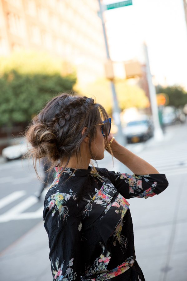 Updos with braids: Side shot of a woman with chocolate brown hair styled into a low bun with a diagonal Dutch braid.