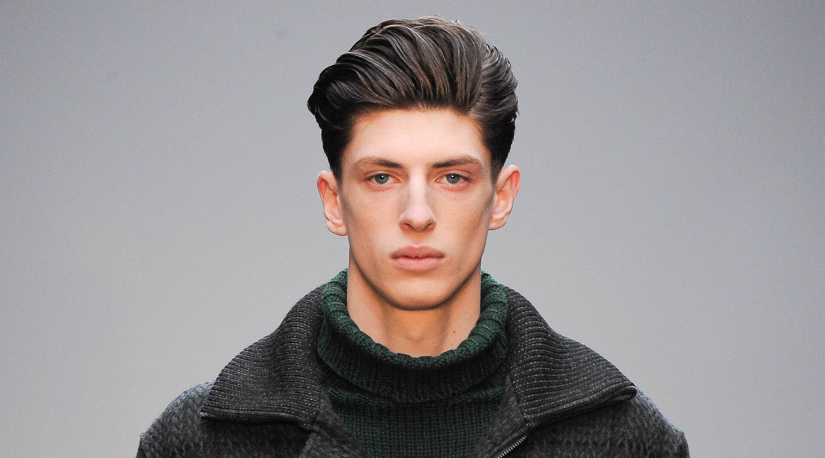 man with dark hair on the runway styled into a swept back quiff