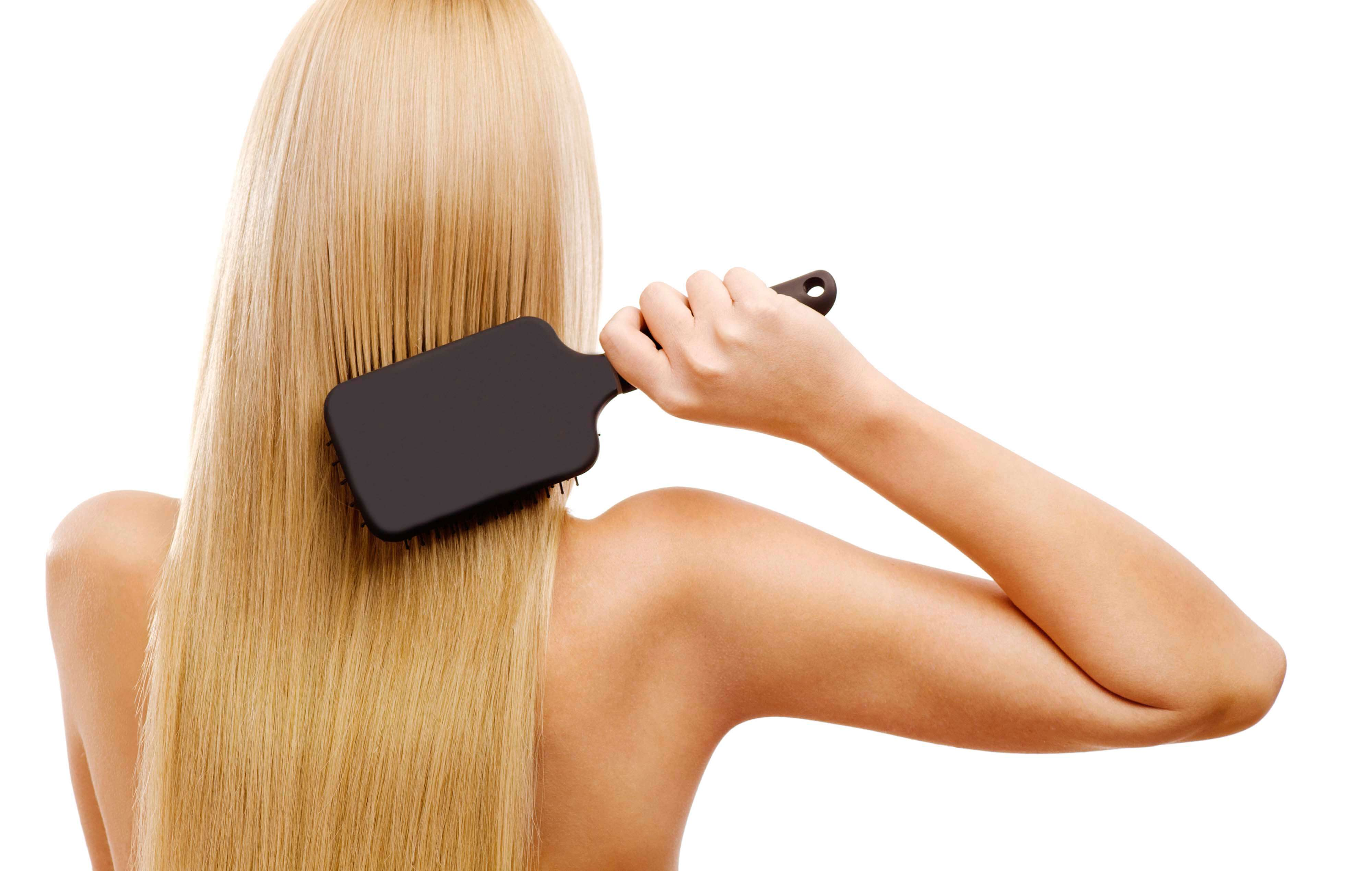 Back view of a blonde woman using a paddle brush
