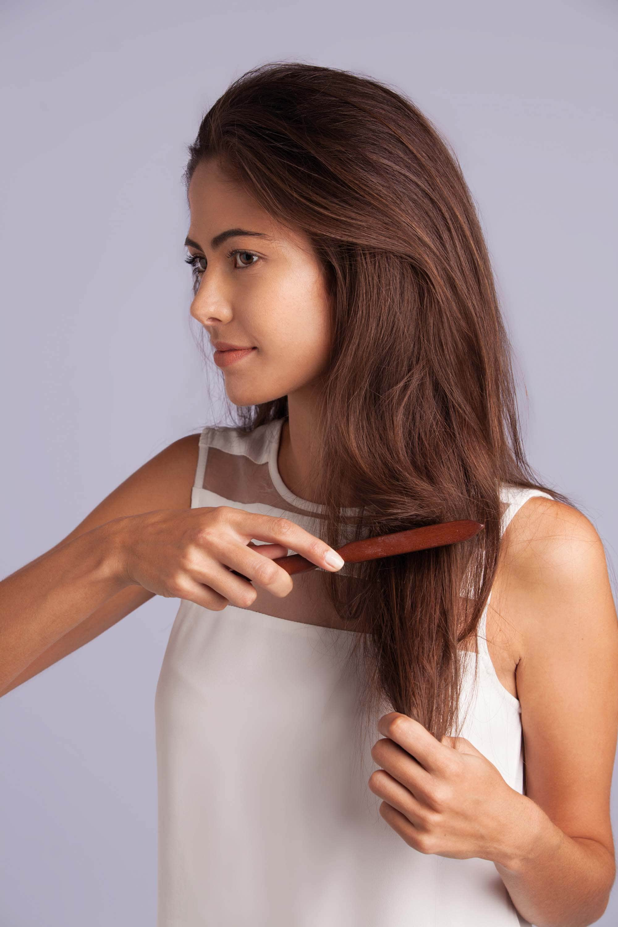 How to get thicker hair: Brunette woman brushing her hair, wearing a white sleeveless top in front of a purple studio background