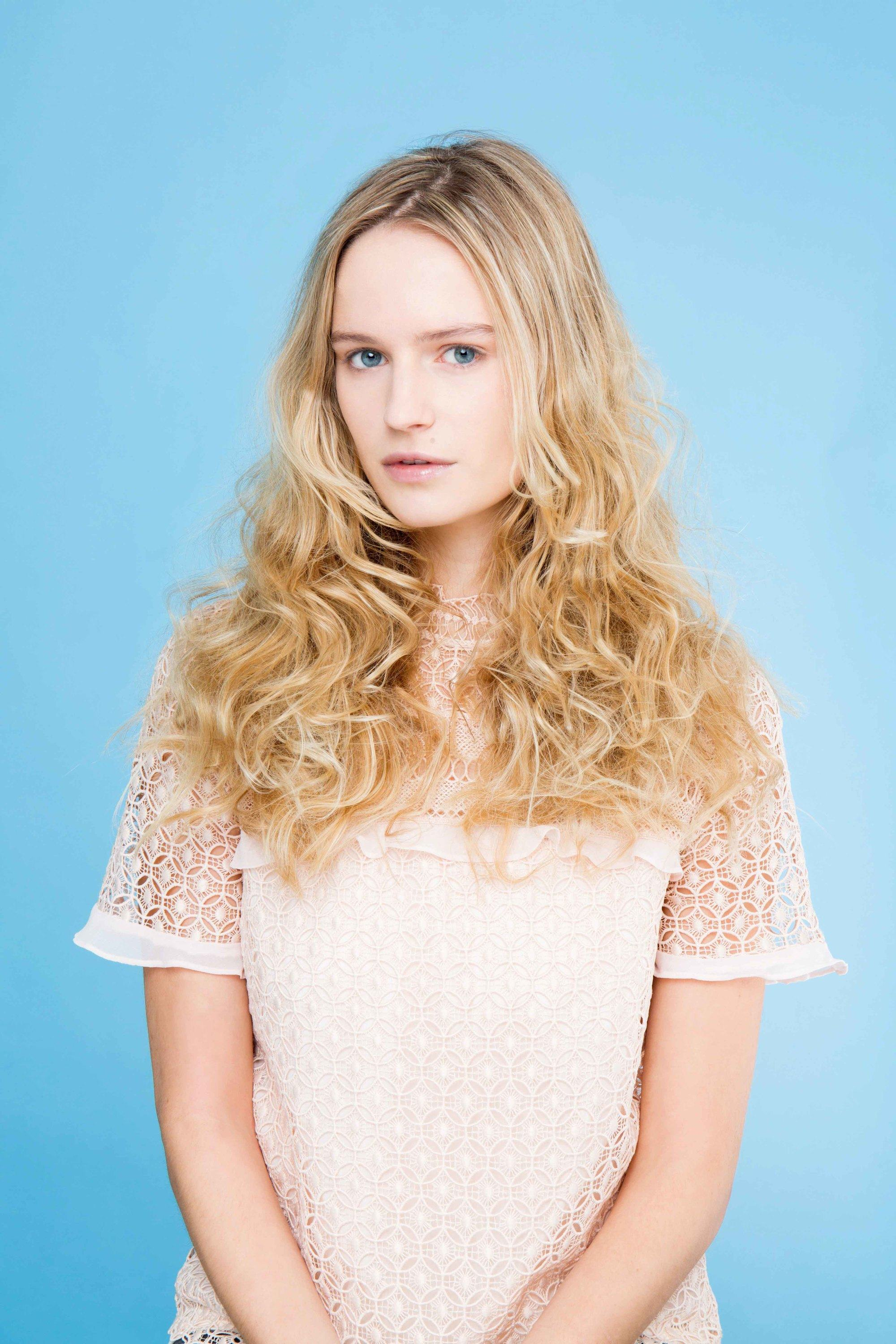 How to use a curling wand: Blonde model with curly ends, wearing a white lace top