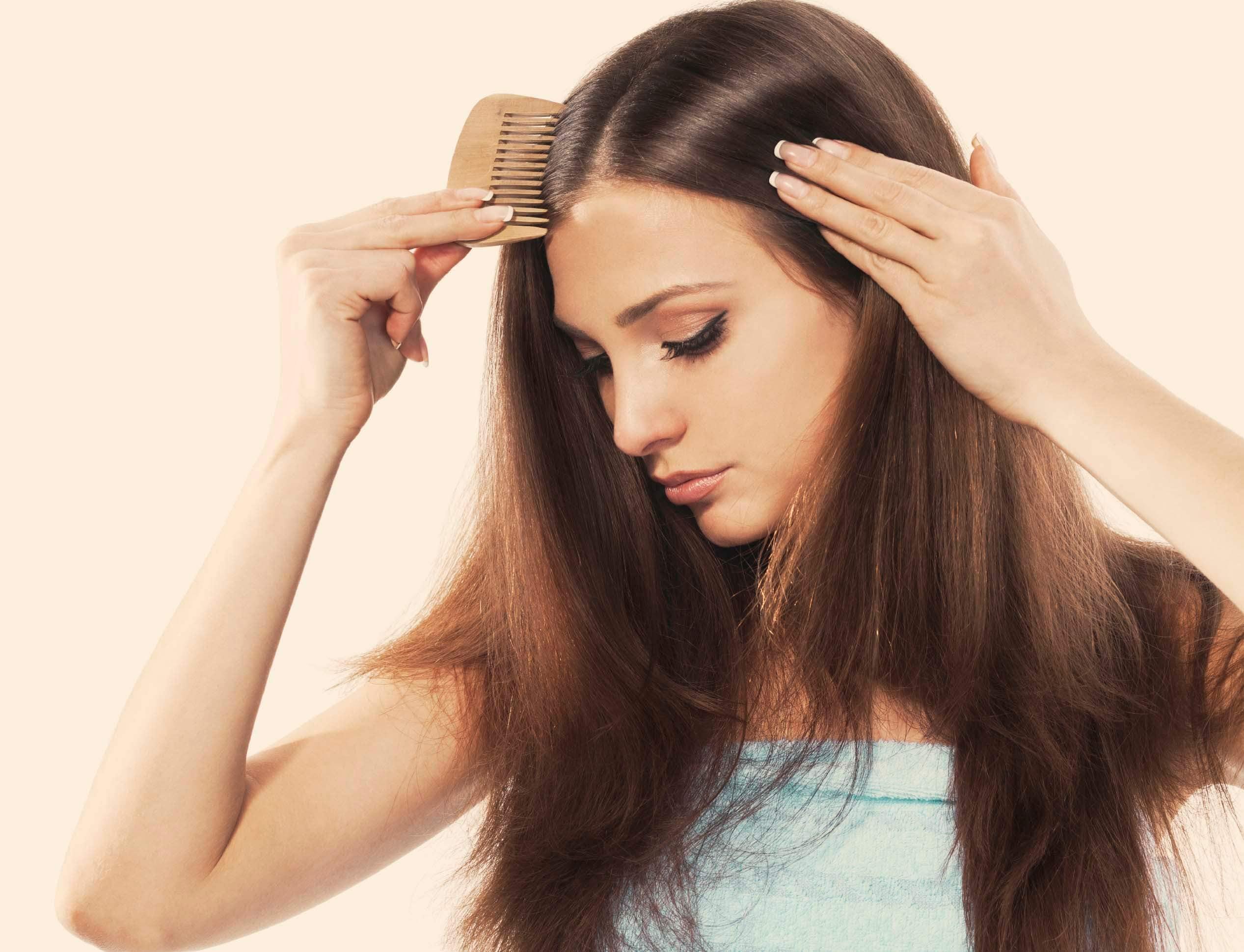 dry scalp vs dandruff woman with hair brush