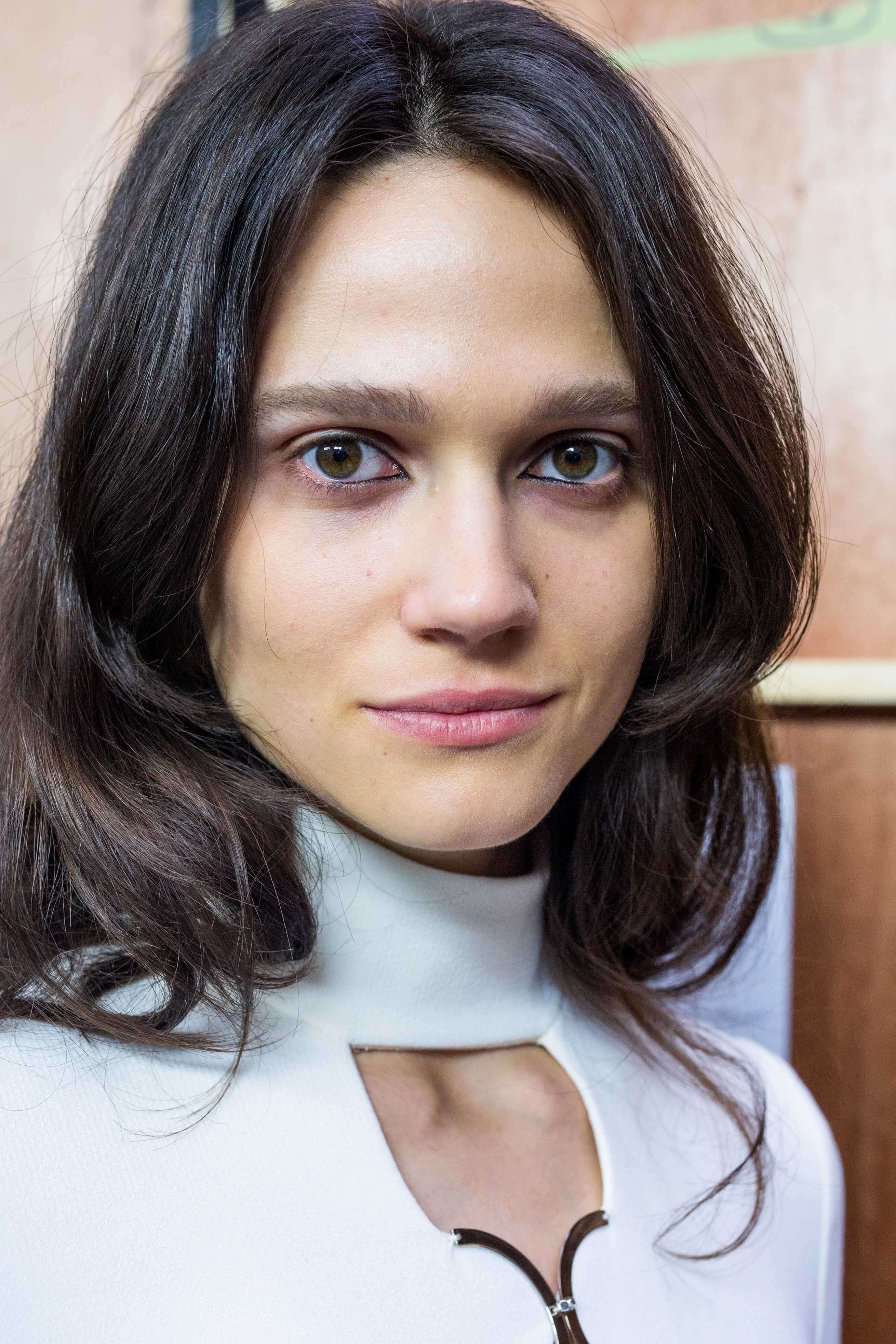 Woman with cool neutral brown hair wearing a white keyhole top