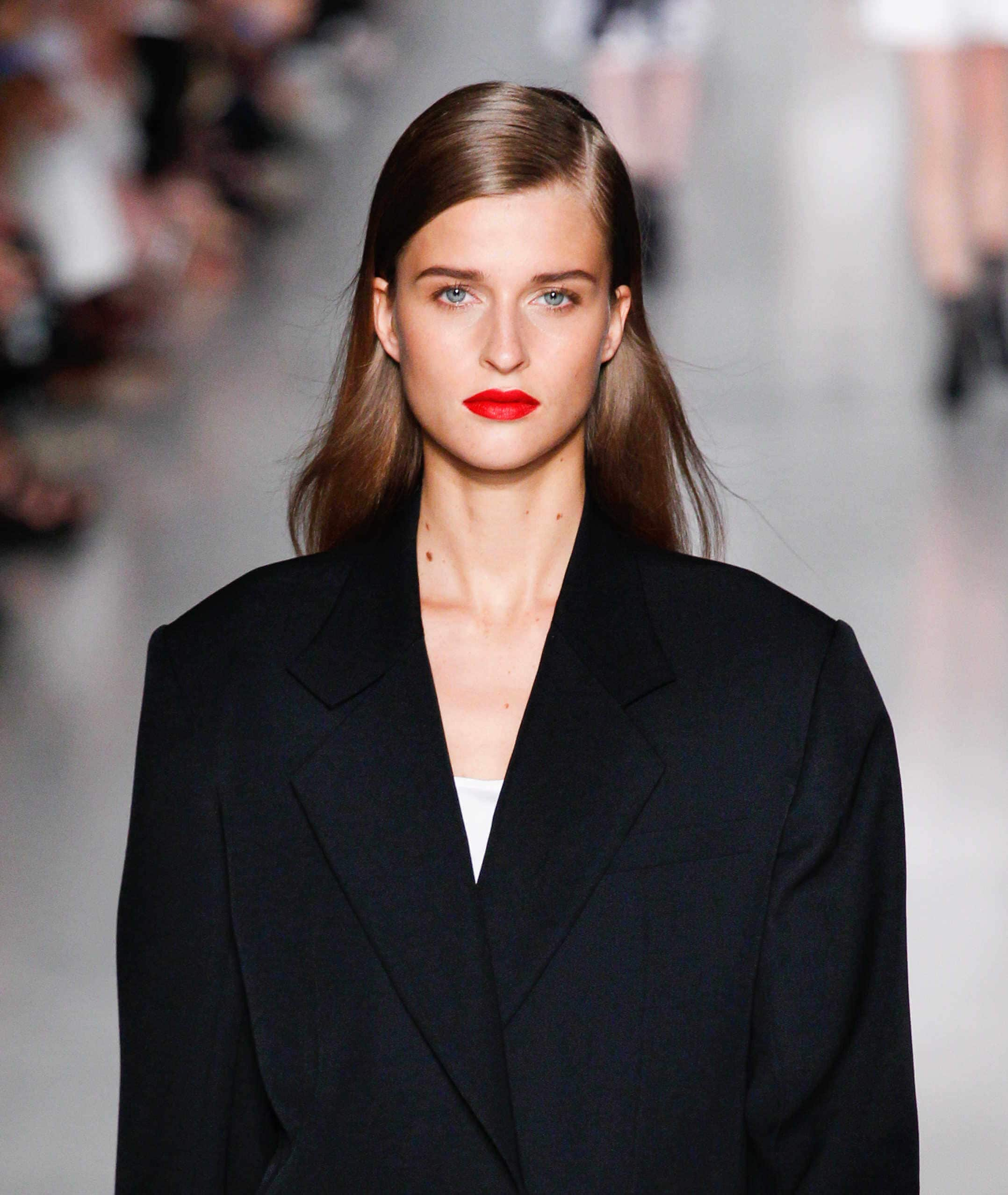 Hairstyles for round faces: Brunette woman with a side parting wearing red lipstick