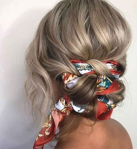 Updos with braids: Back shot of a woman with ash blonde hair styled into a scarf braided low bun hairstyle.