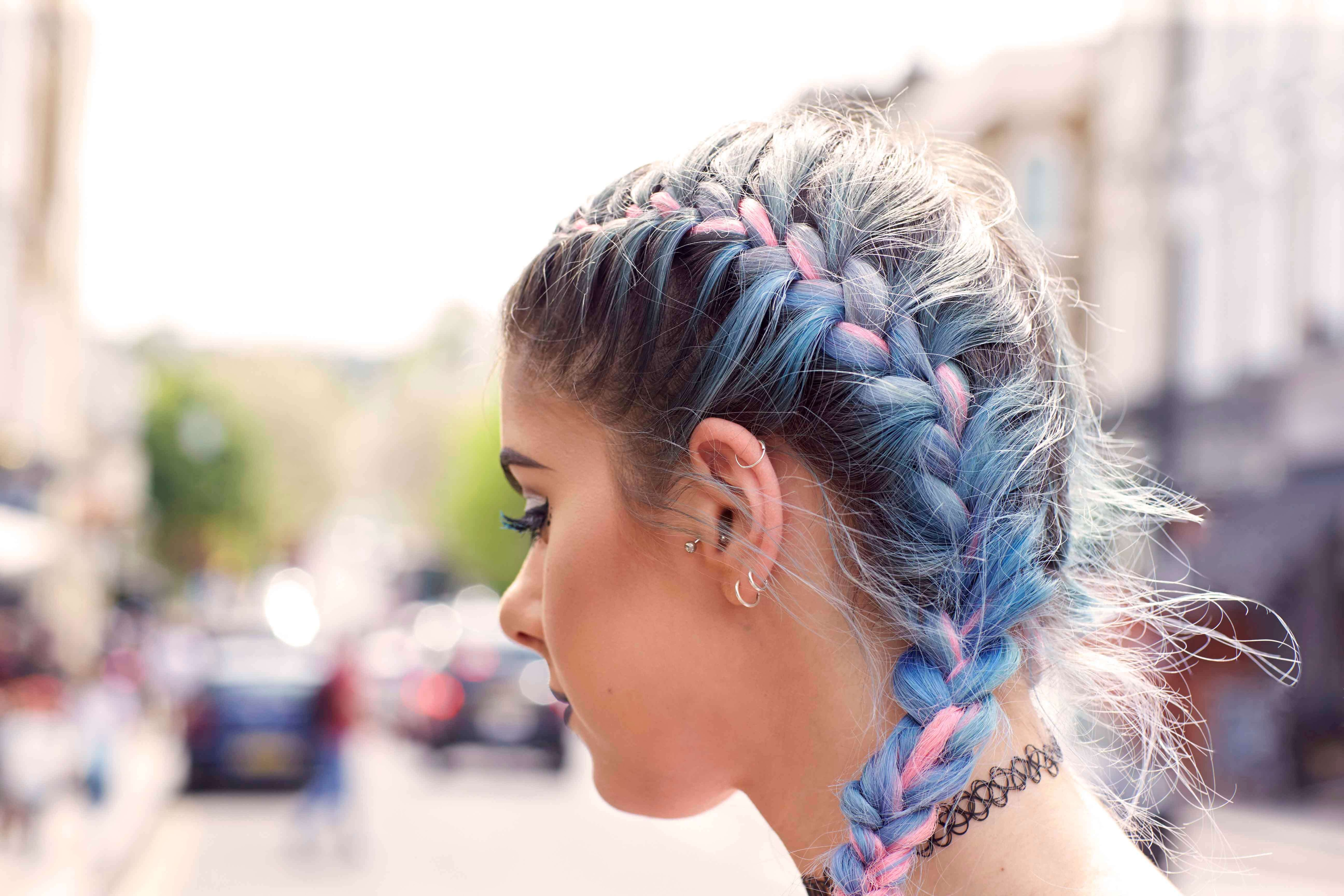 French braid hairstyles: Double French plait on a young woman with blue and pink coloured hair