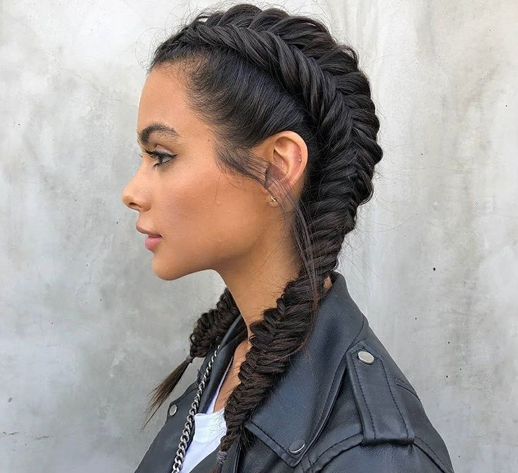 Updos with braids: Side shot of a woman with dark hair styled into a fishtail boxer braids.