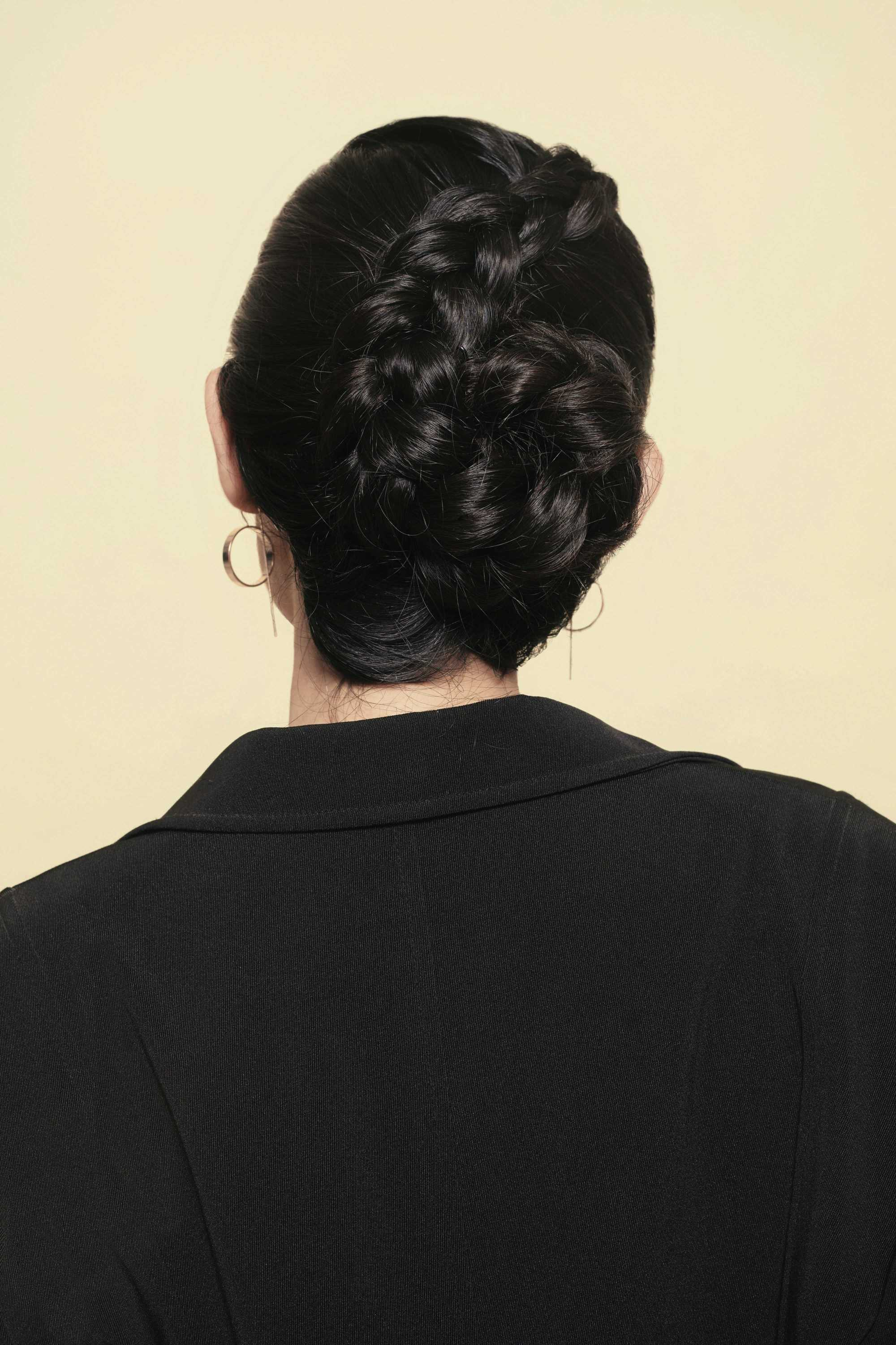 Updos with braids: Back shot of a woman with flower braided bun updo.