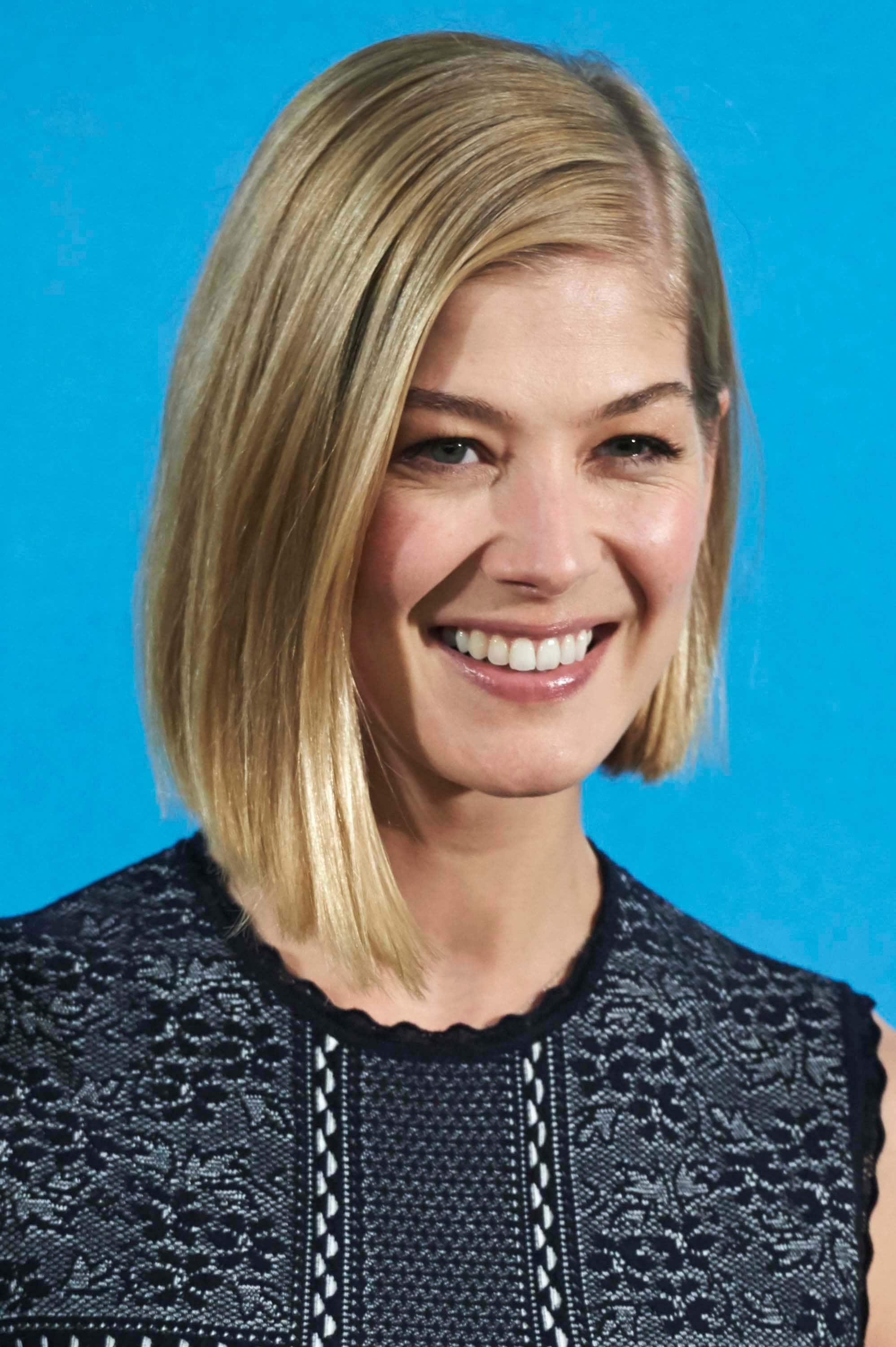 Rosamund Pike with side part golden blonde graduated bob hair