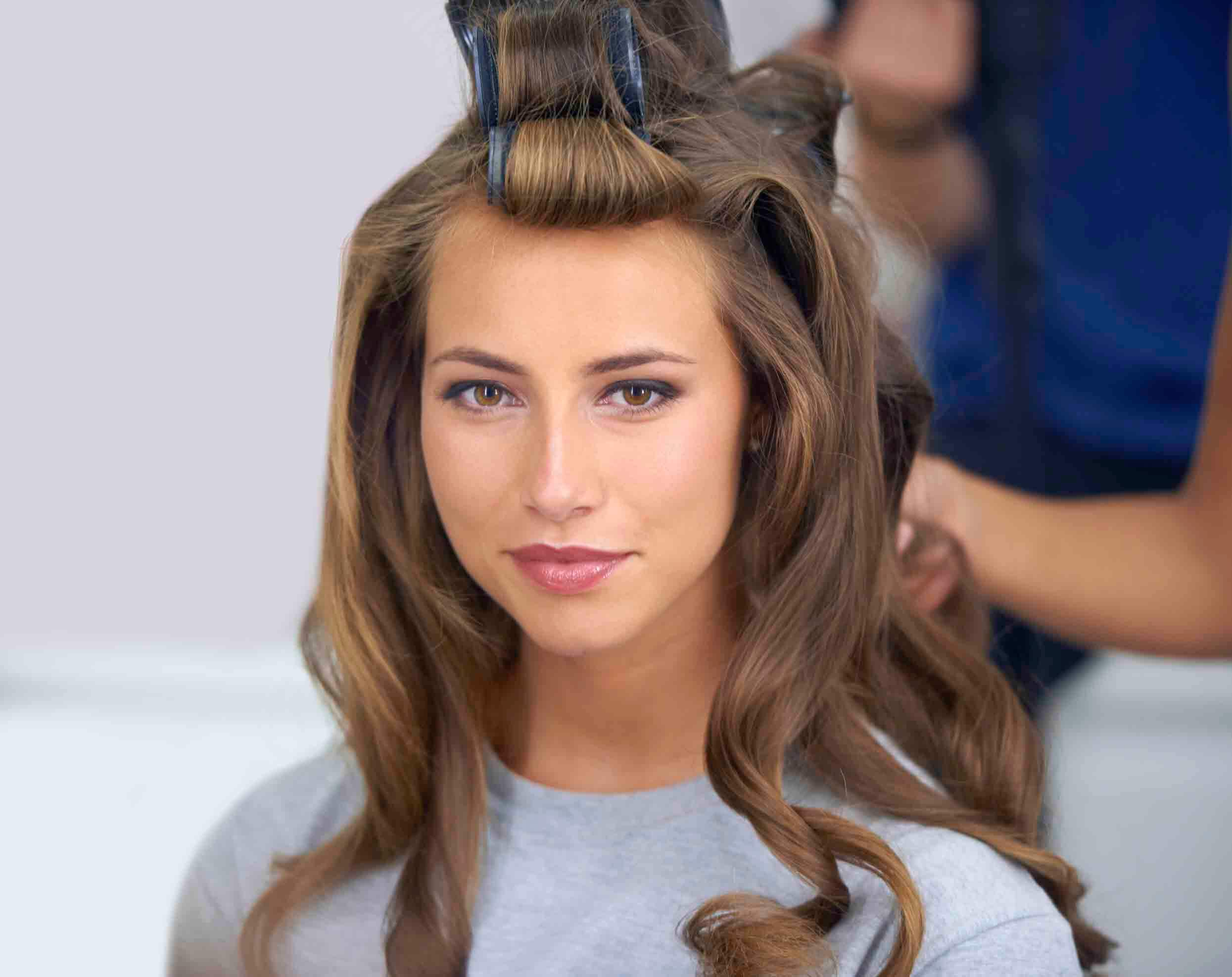 How to get thicker hair: Brunette woman with her hair in rollers, having her hair done