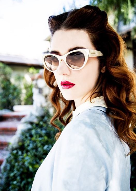 Woman with deep red wavy long hair and double quiff wearing sunglasses