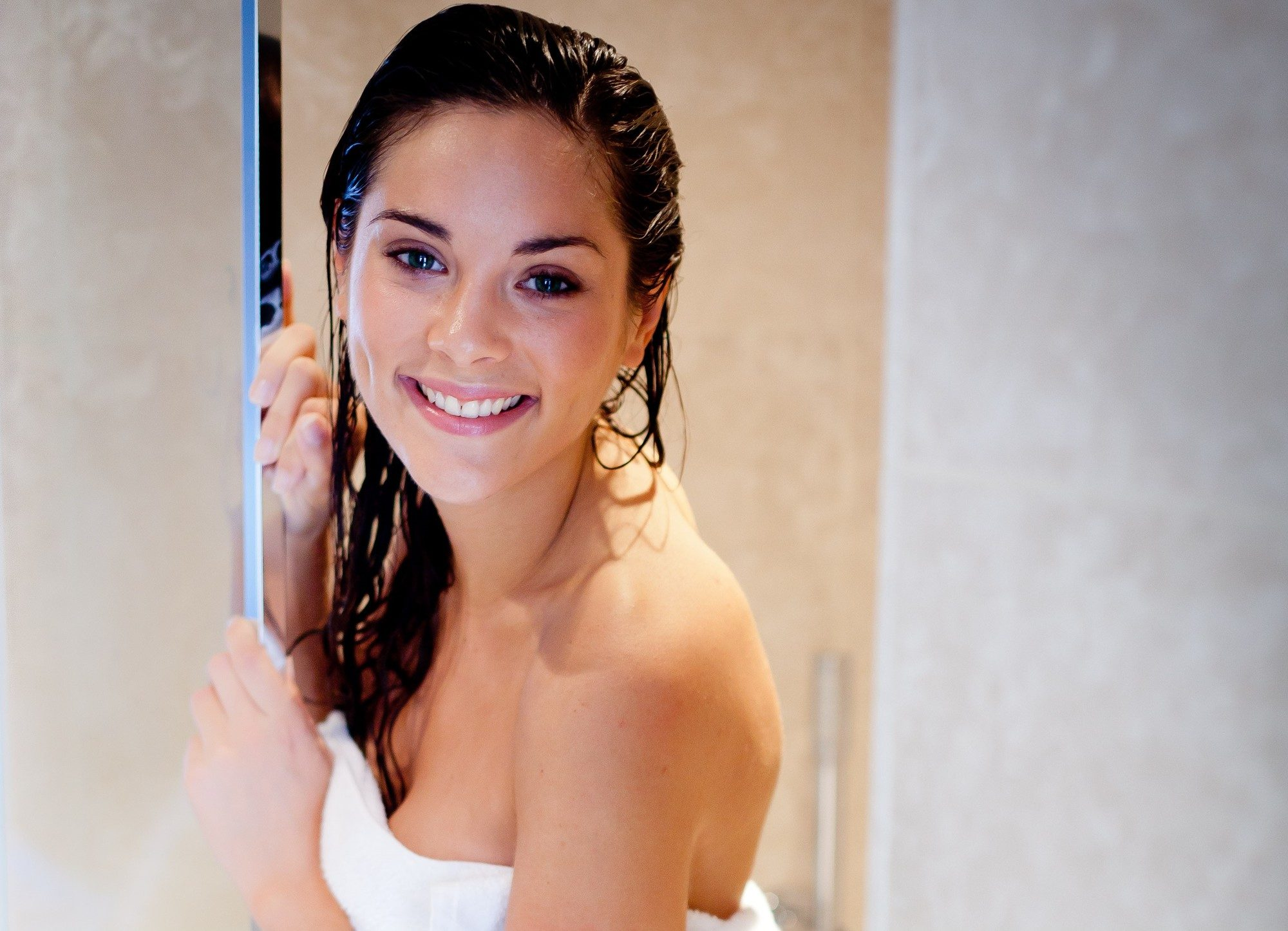 brunette woman in the shower in a towel with wet hair