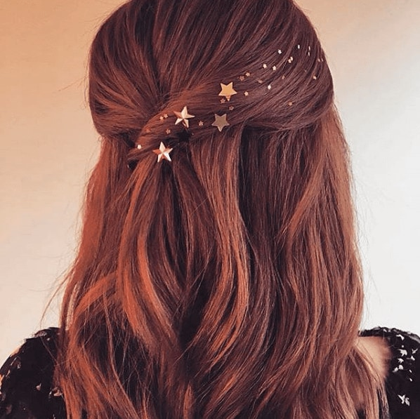 Hair trends: Woman with medium length auburn hair in half-up, half-down with stars accessories.