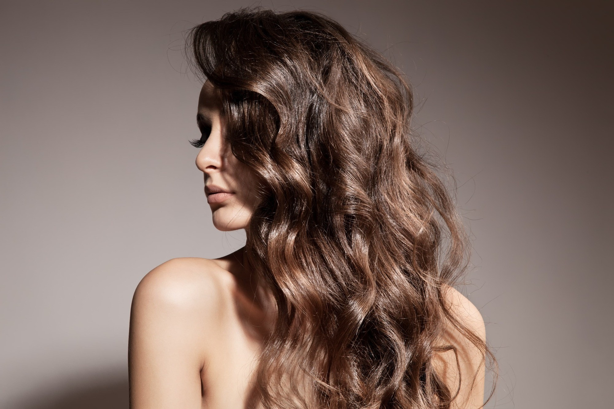 How to use a curling wand: Brunette model with long curly hair, worn to one side