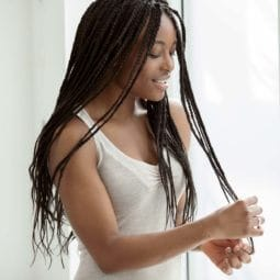 box-braids-black-hairstyles of a black woman touching her hair