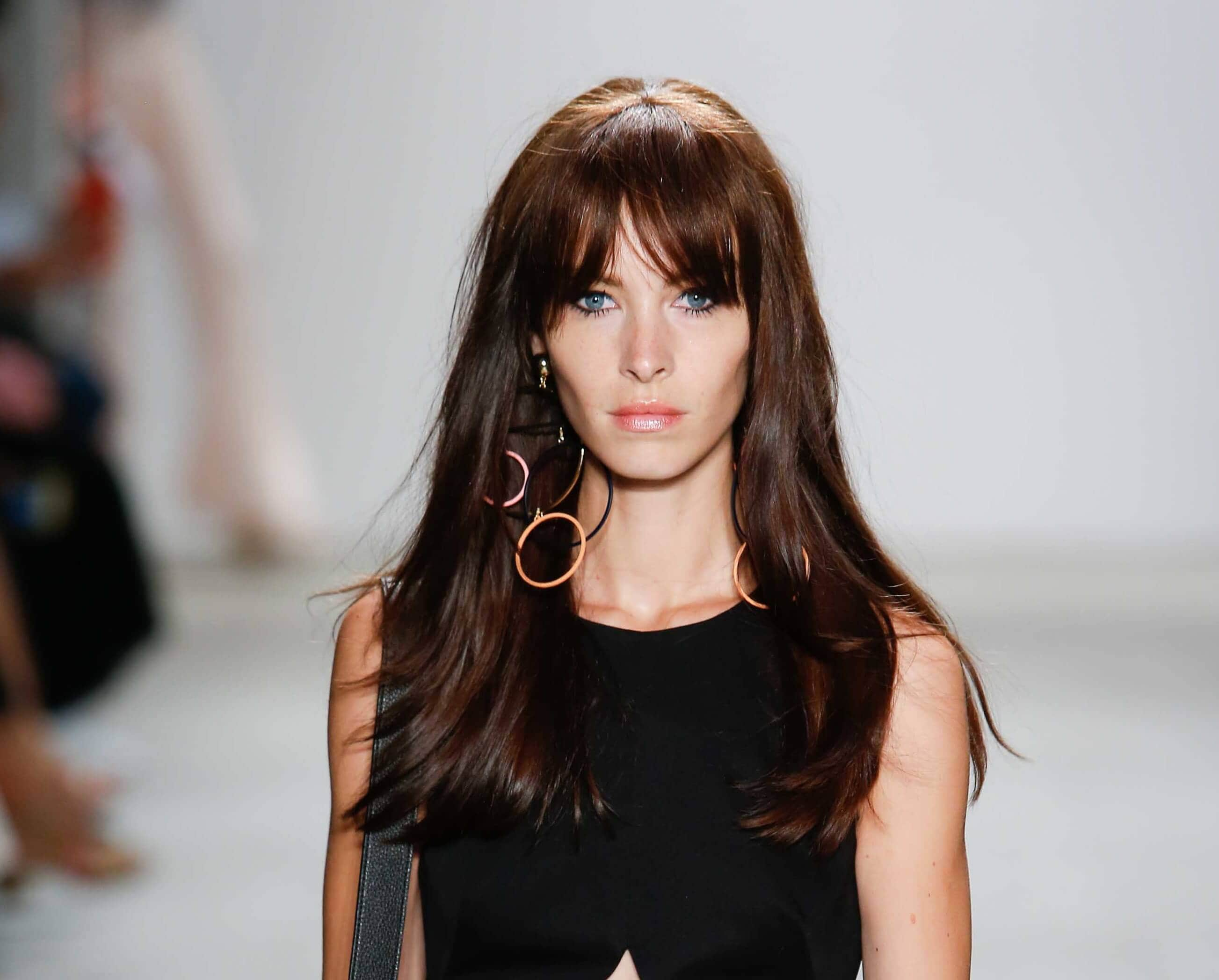 Woman with mid length brown hair with a tinge of red