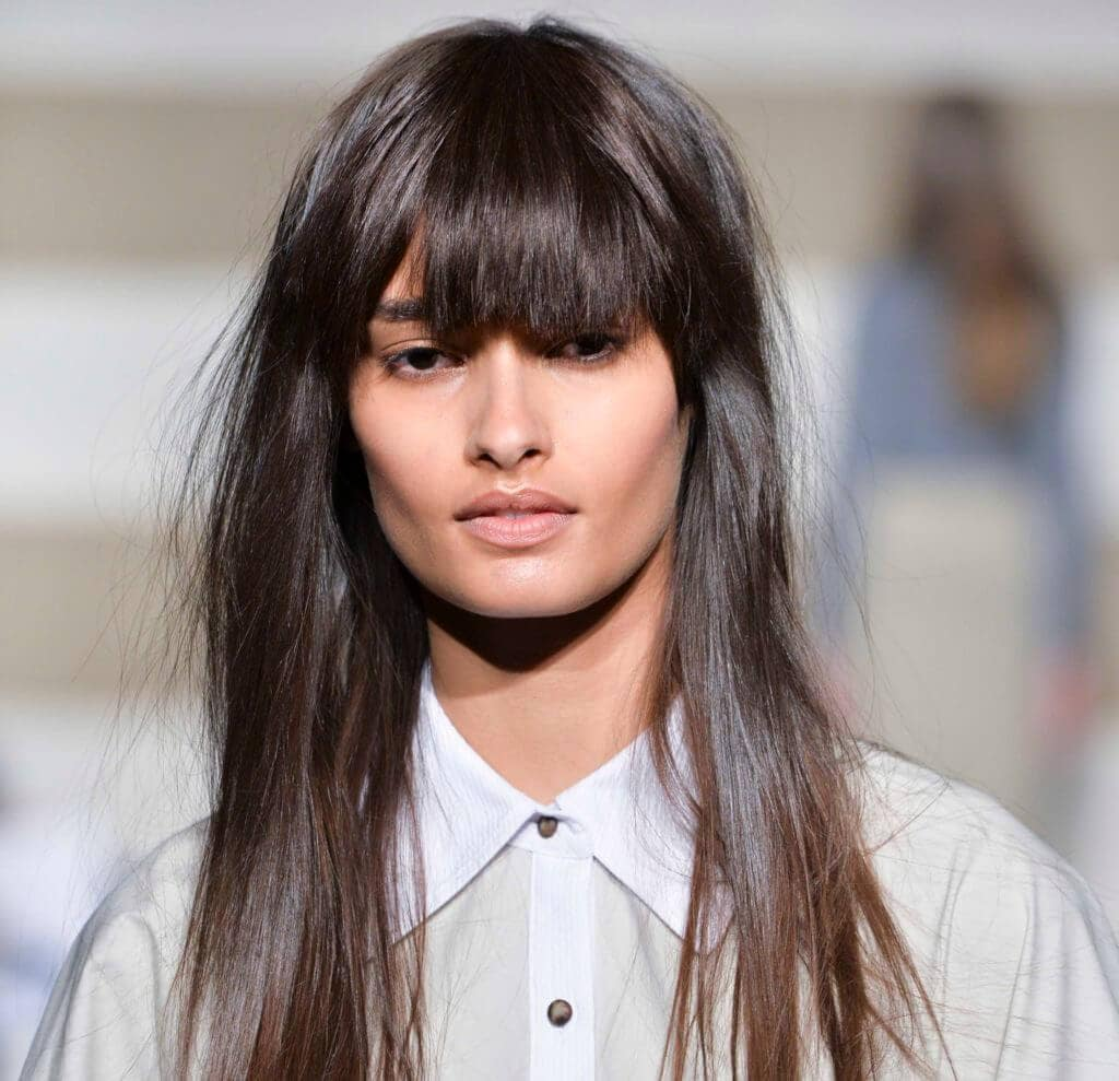 woman on the runway with long dark brown hair worn straight and with a full fringe cut in