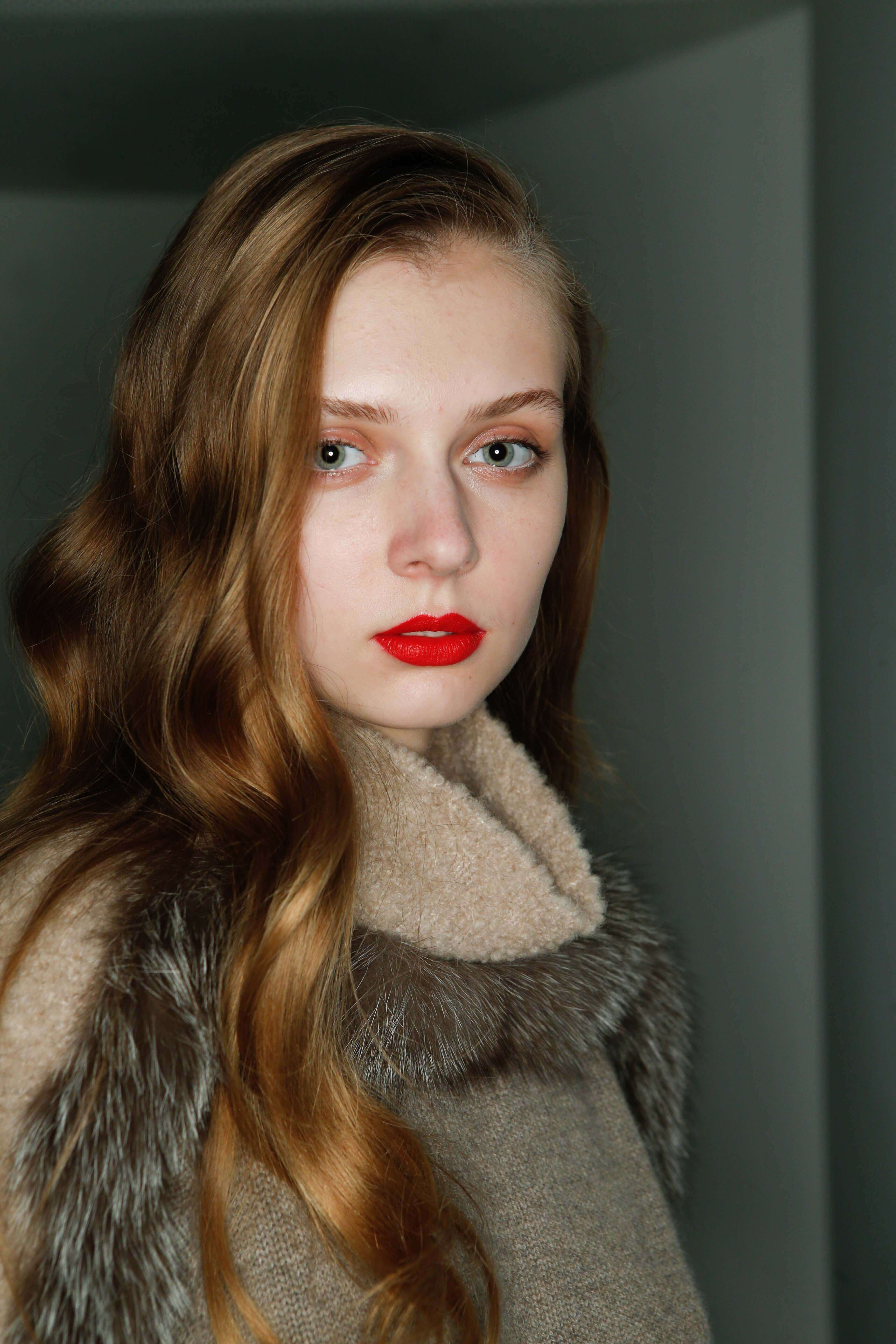 How to use a curling wand: Redhead model with sleek wavy hair, wearing red lipstick