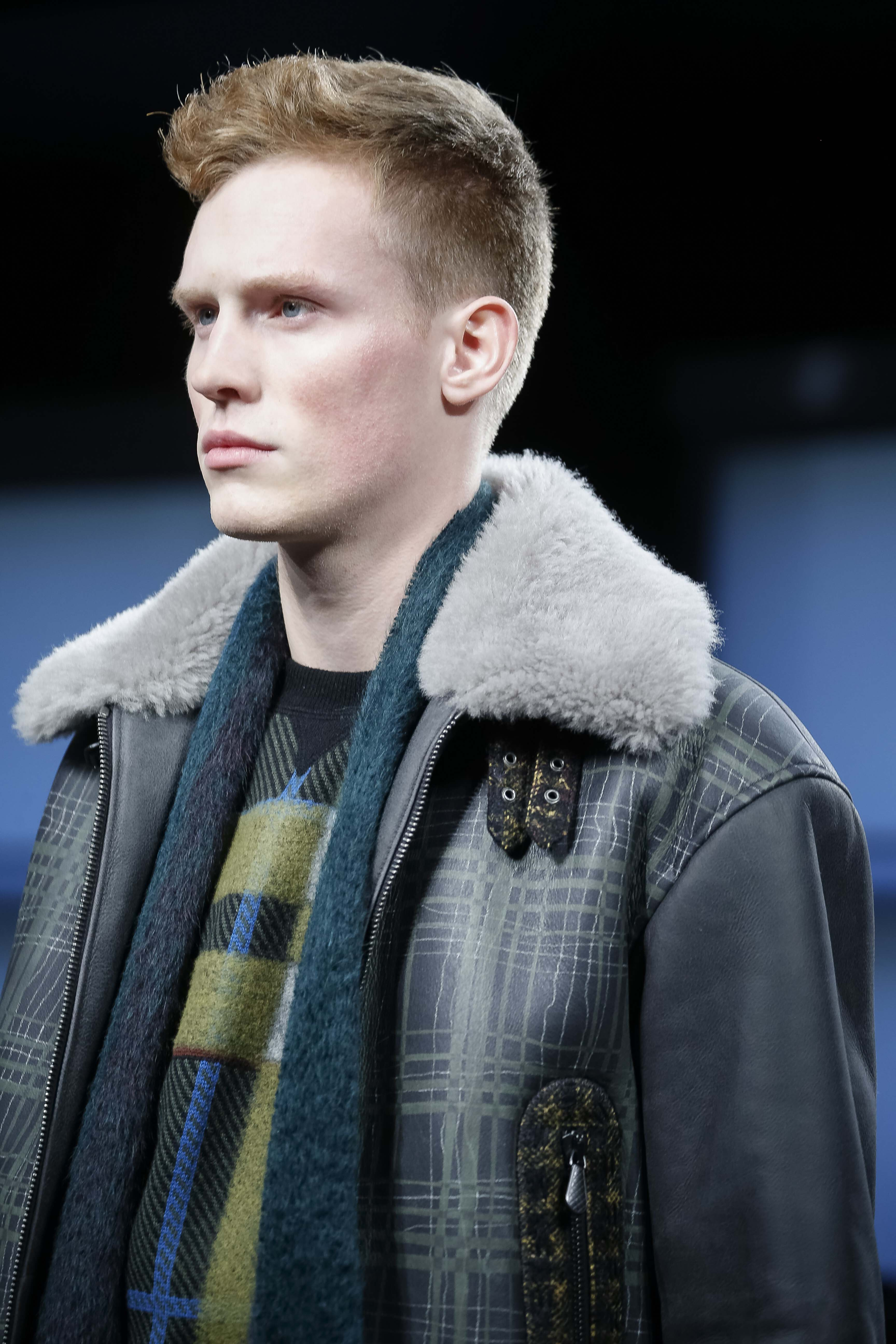 man with short blonde hair styled into a quiff hairstyle wearing a shearling coat on the runway