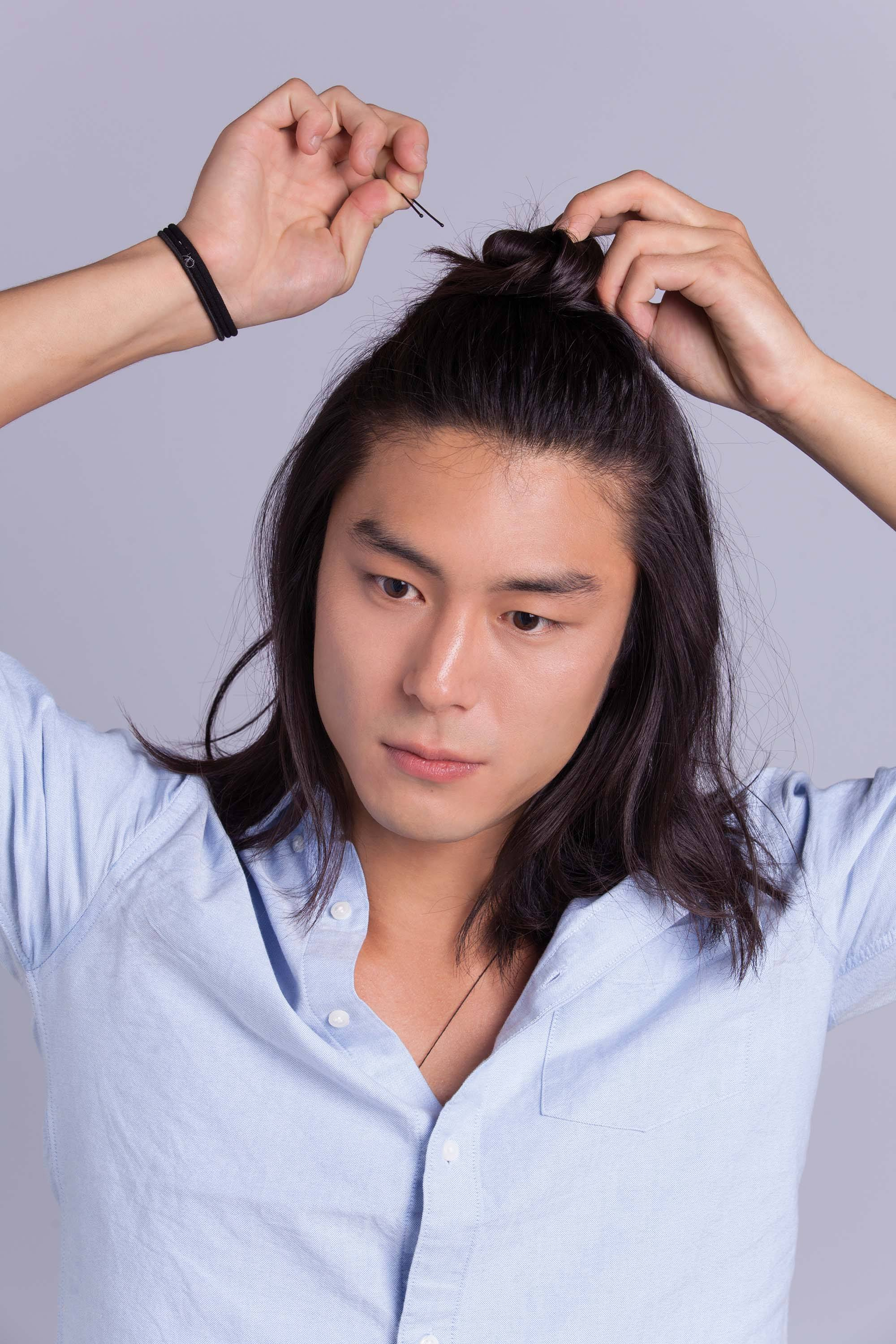 Asian man bun: Asian male model with shoulder-length hair securing half-up man bun