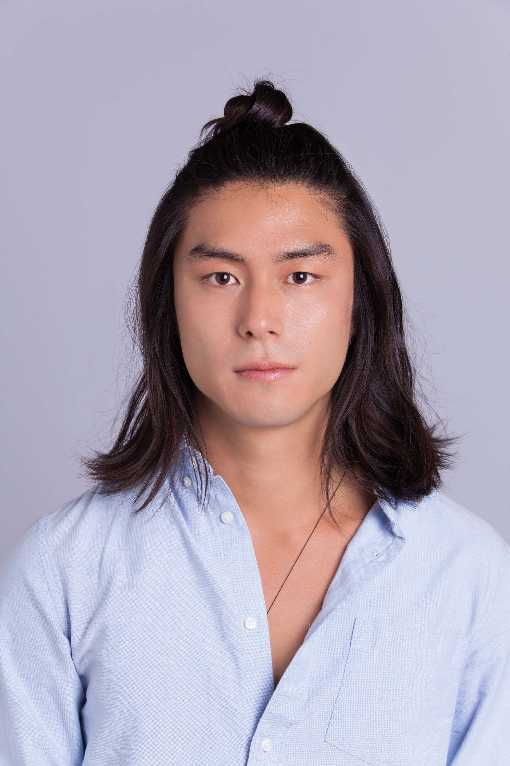 Asian man bun: Asian male model with shoulder-length hair with the final half-up man bun