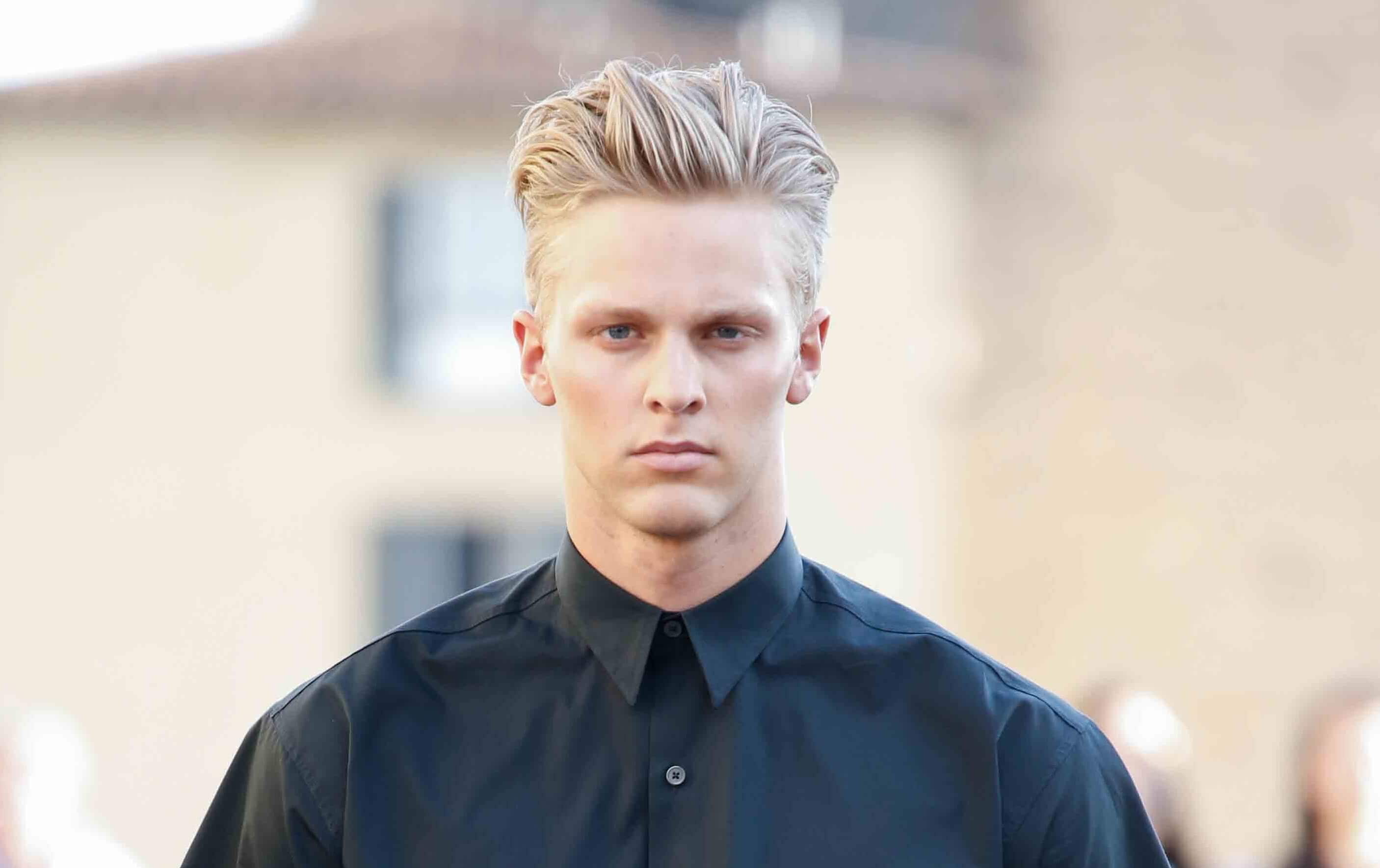 man with blonde hair cut short on the sides and swept up into a quiff on top