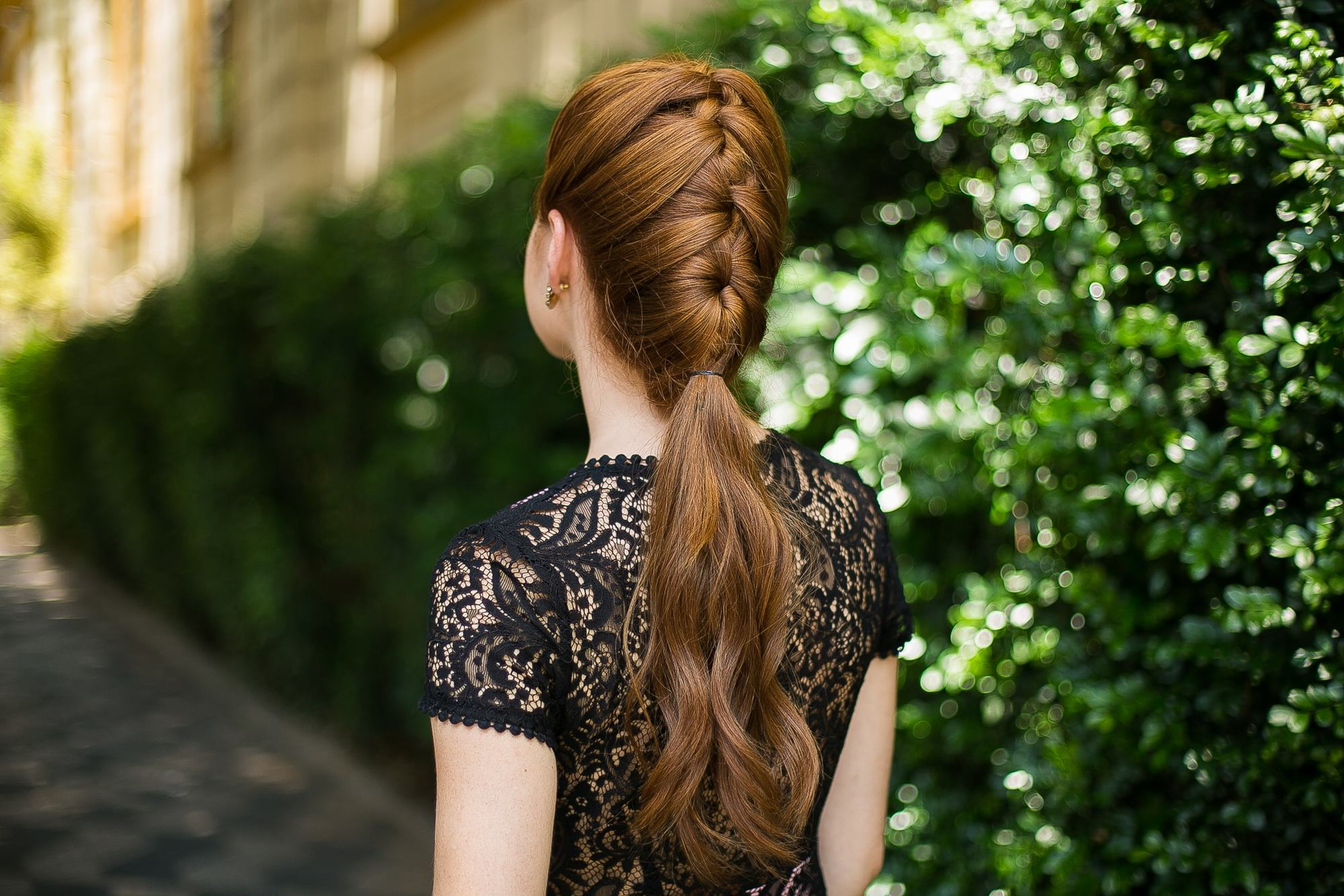 Updos with braids: Back shot of a woman with a French braided ponytail