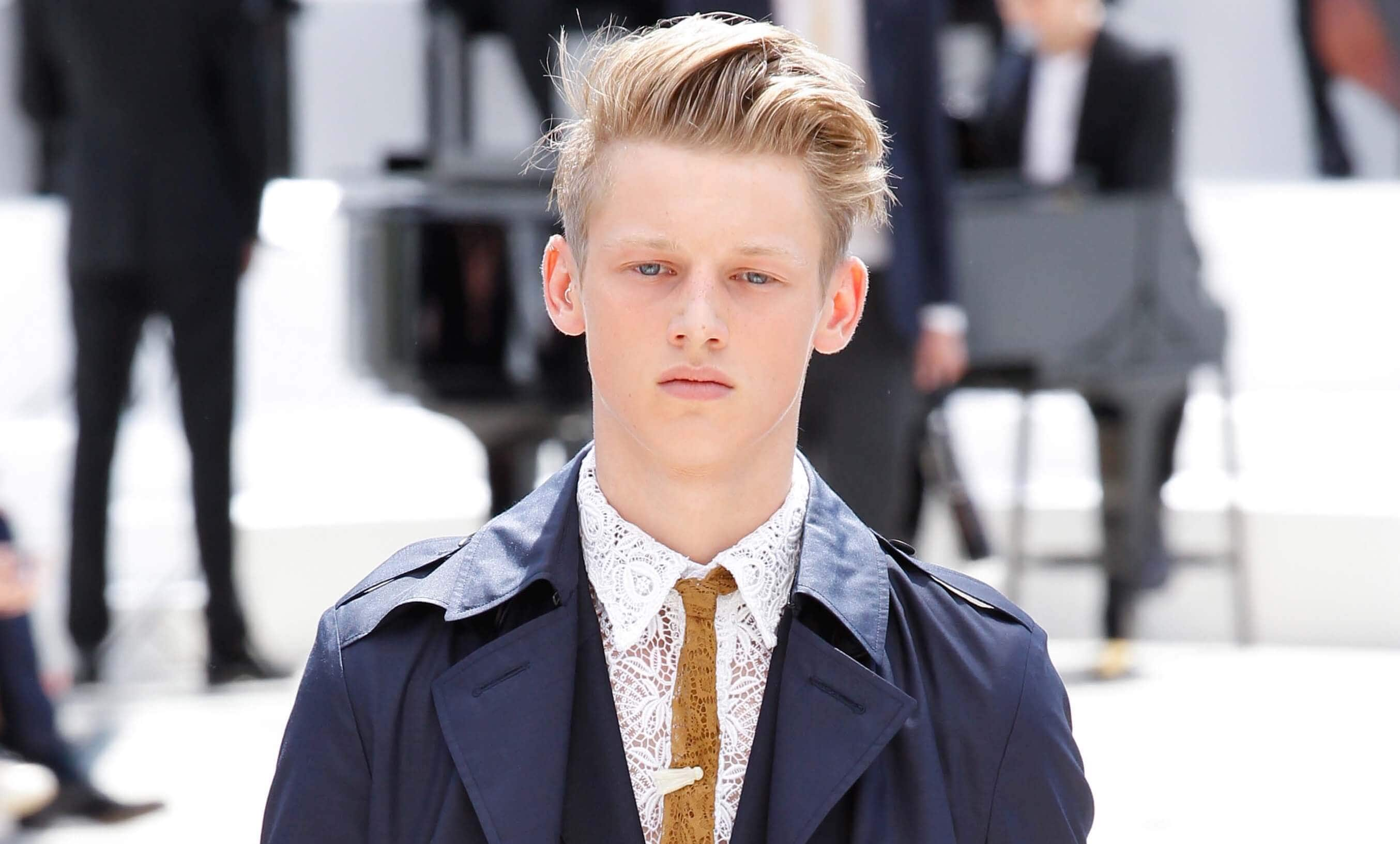 man with blonde hair styled into a quiff walking on the runway wearing a classic navy blue outfit