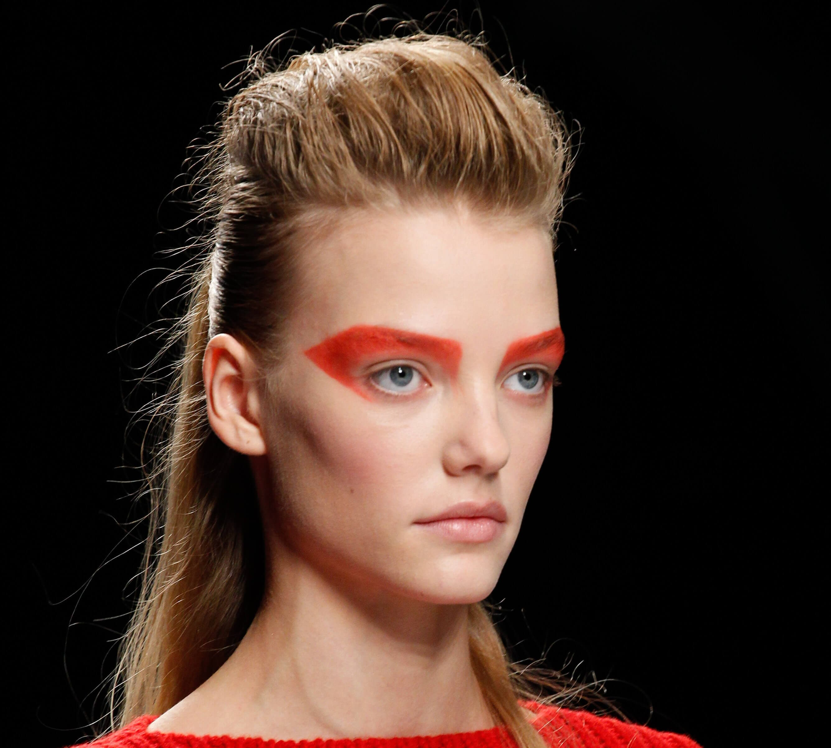 Medium length hairstyles for fine hair: Woman with blonde straight hair styled in a ponytail with a retro quiff with bold red eyeshadow on runway.