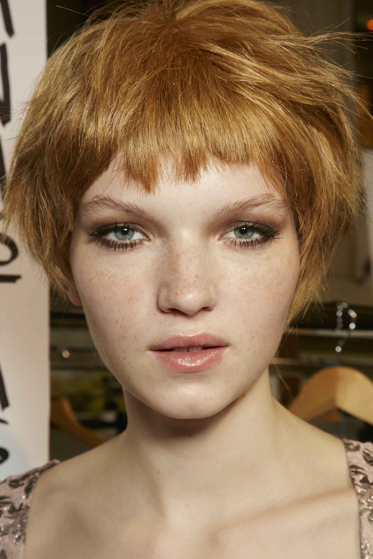 Short bangs: Model with short choppy strawberry blonde hair and micro bangs.