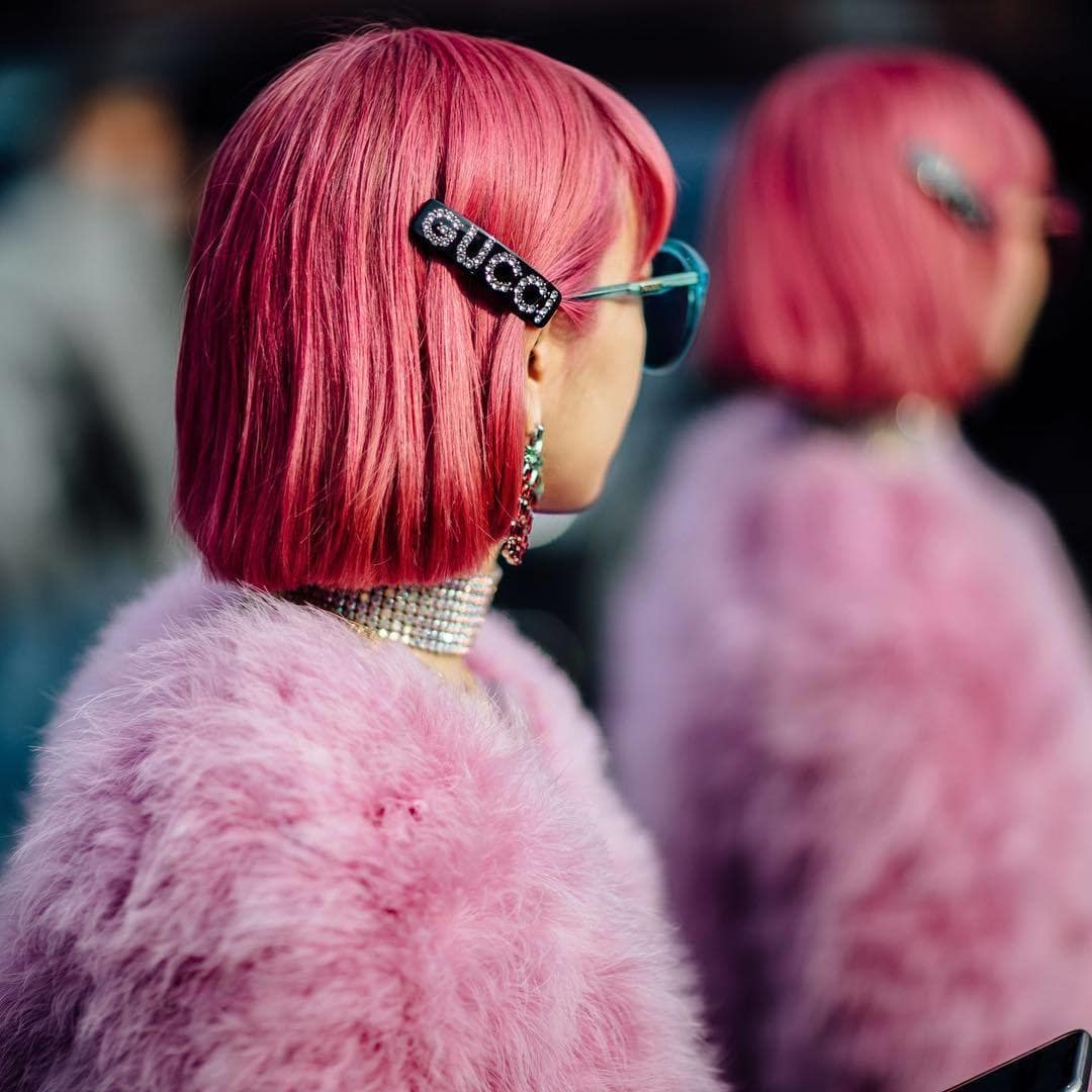 VO5 Hot Oil: Side shot of a woman with pink bob hairstyle with Gucci slide in it, wearing sunglasses and pink fluffy jacket