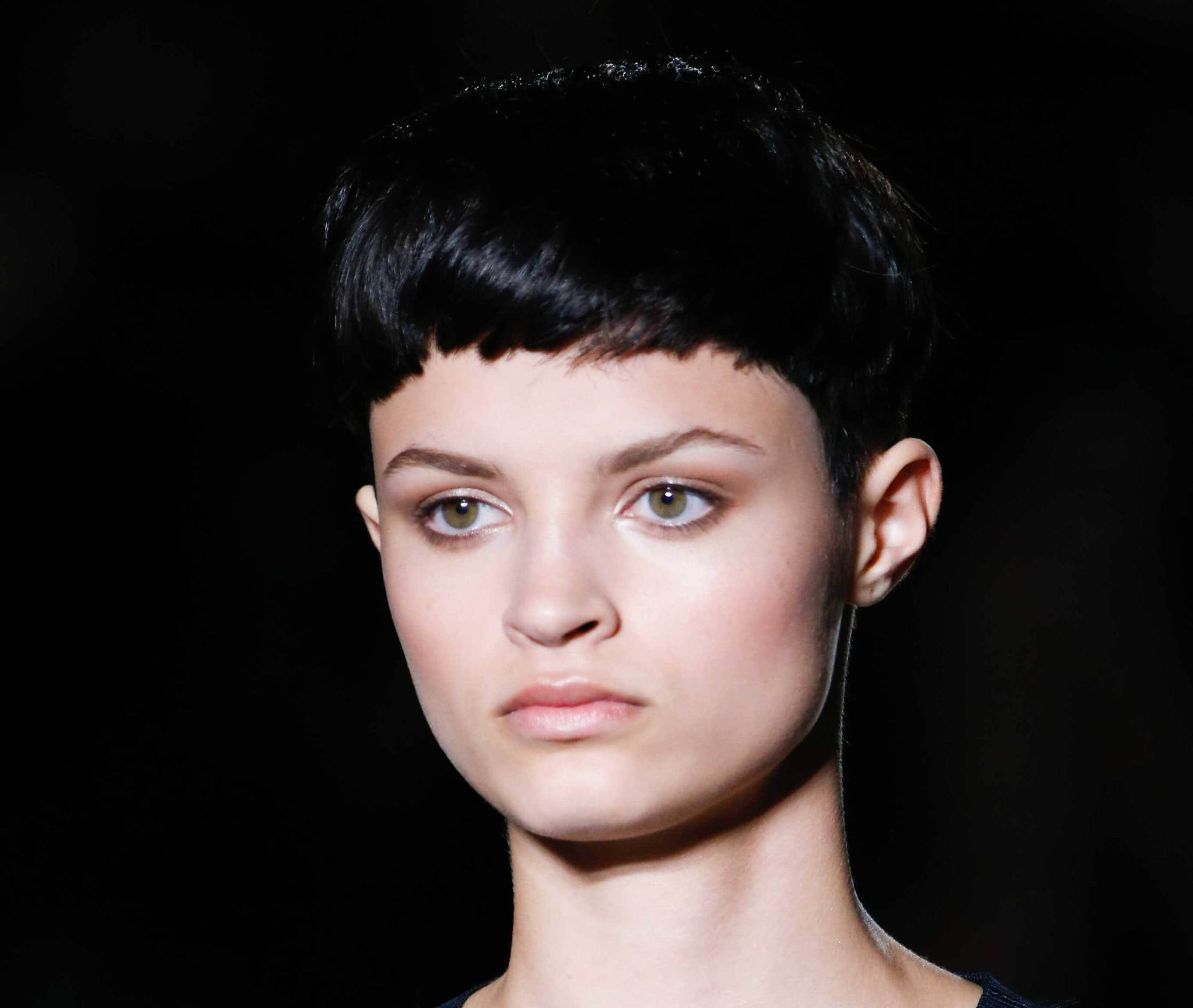 Hairstyles for round faces: Brunette woman with short black bowl cut pixie