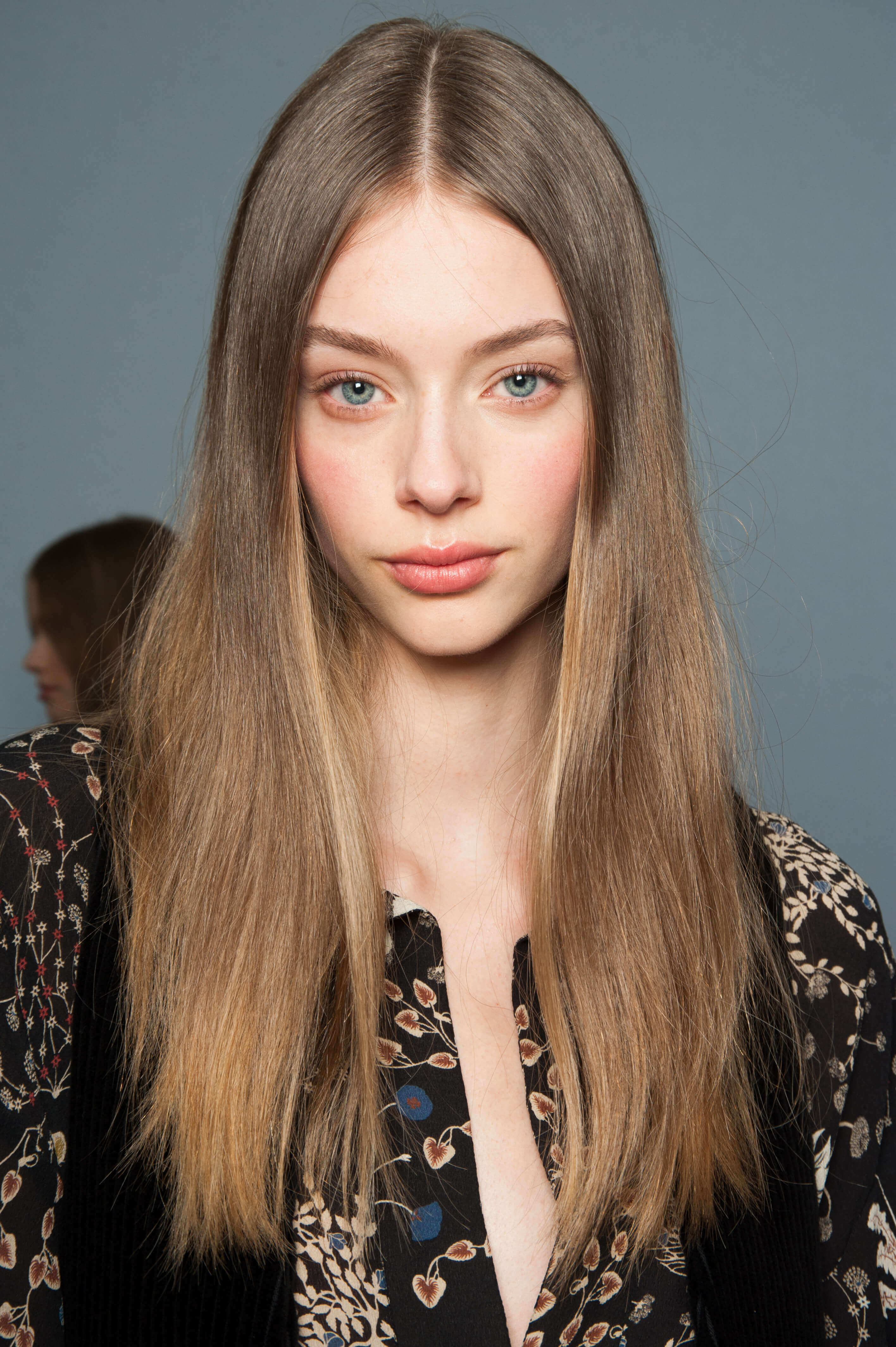 keratin treatment: close up shot of model with sleek, long hair, wearing a floral black dress and posing backstage