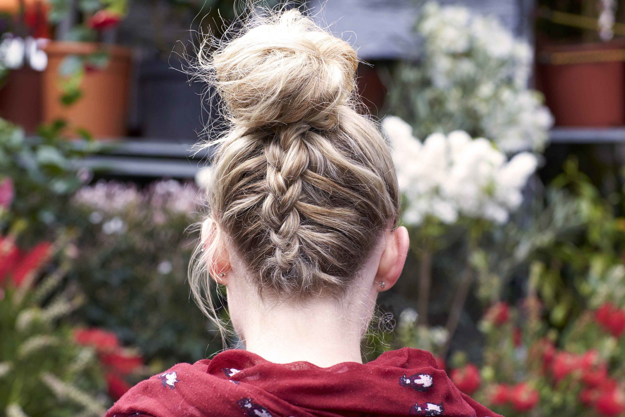 Updos with braids: Back shot of woman with dirty blonde hair styled into an upside down Dutch braided bun.