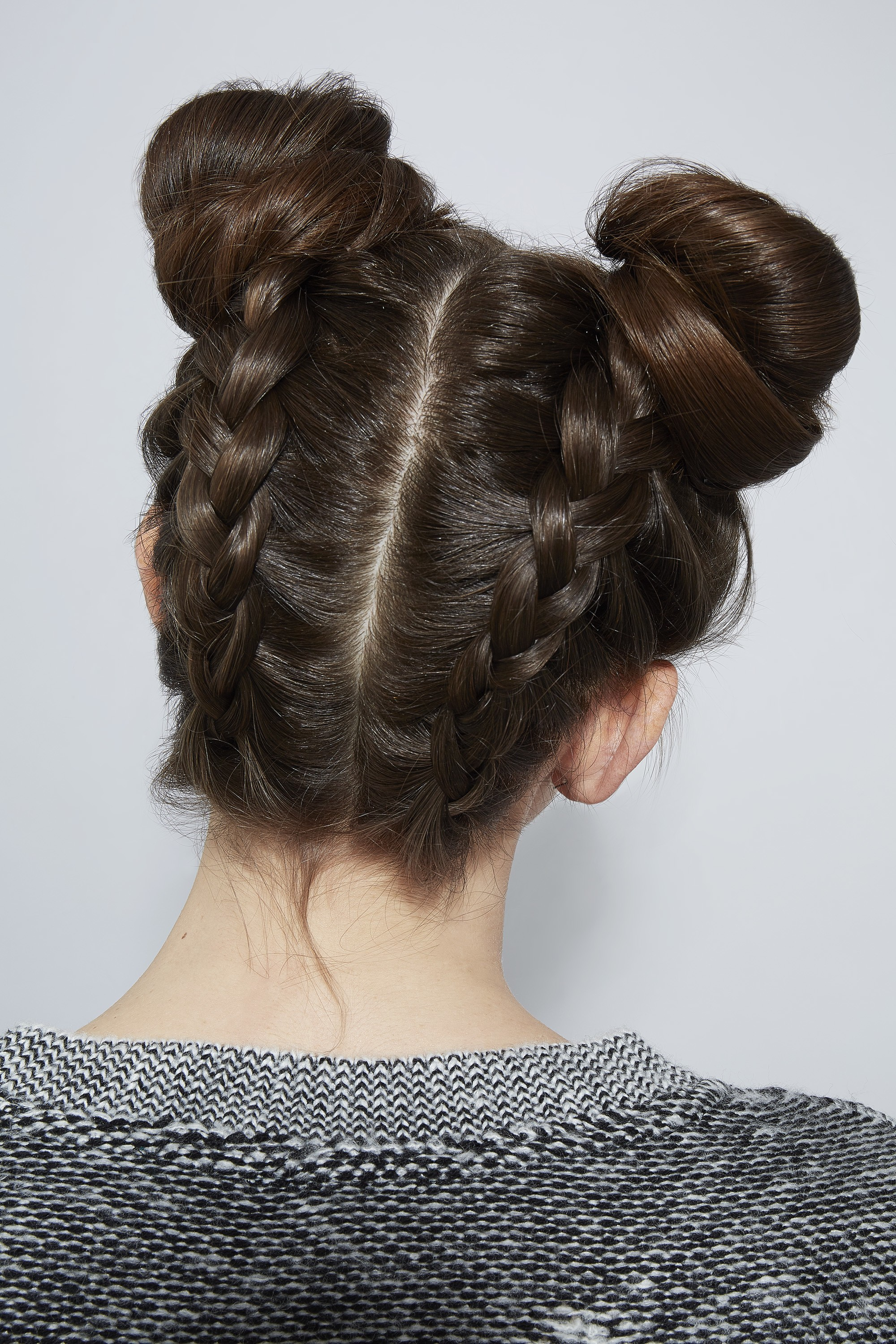 Updos with braids: Back shot of a woman with upside down Dutch braided space buns.