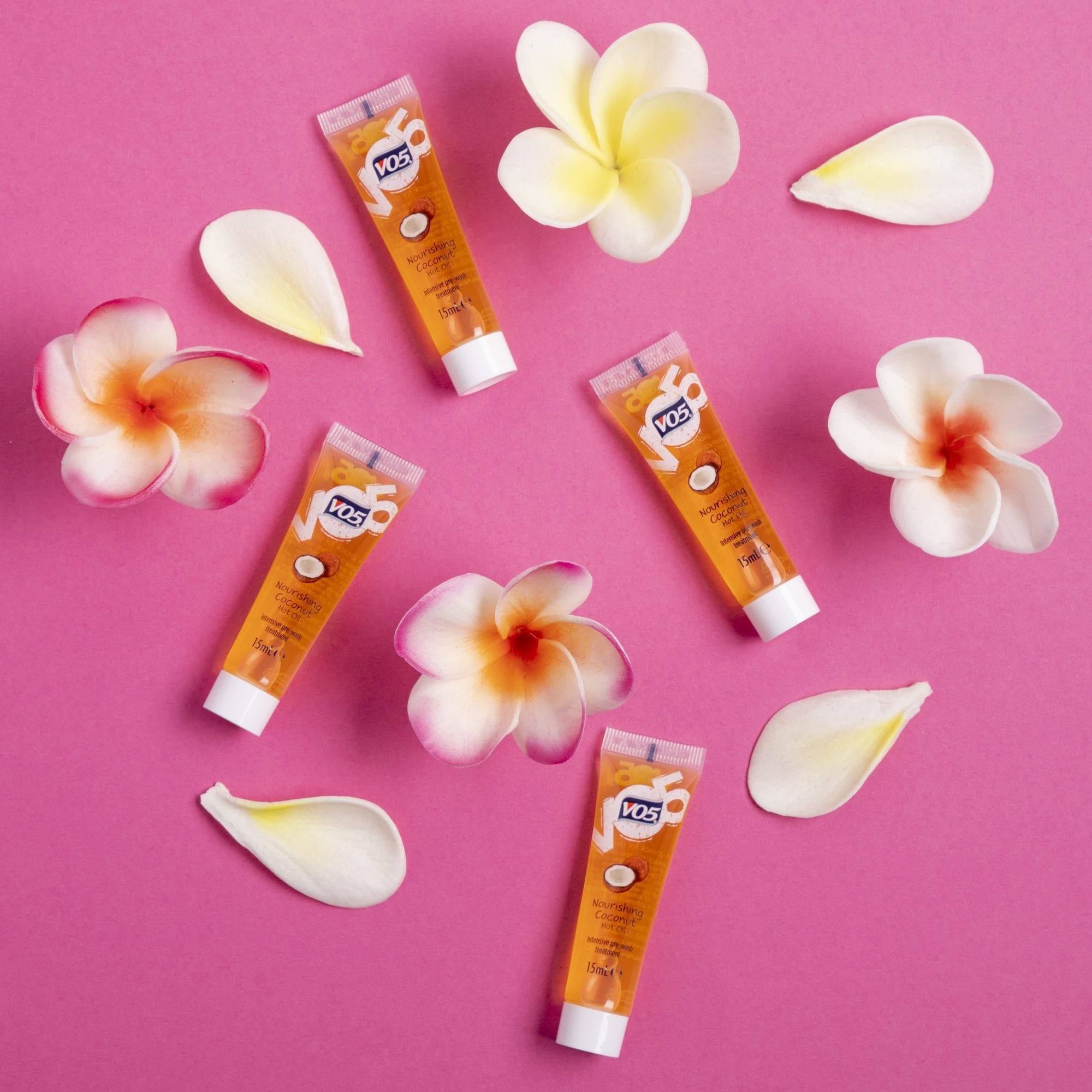 VO5 hot oil: Flat lay of the the new VO5 Nourishing Coconut Oil on a pink background with frangipani flowers dotted around