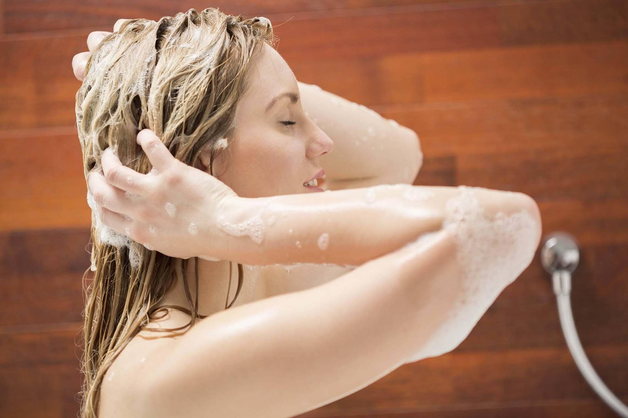 blonde woman in the shower washing her hair