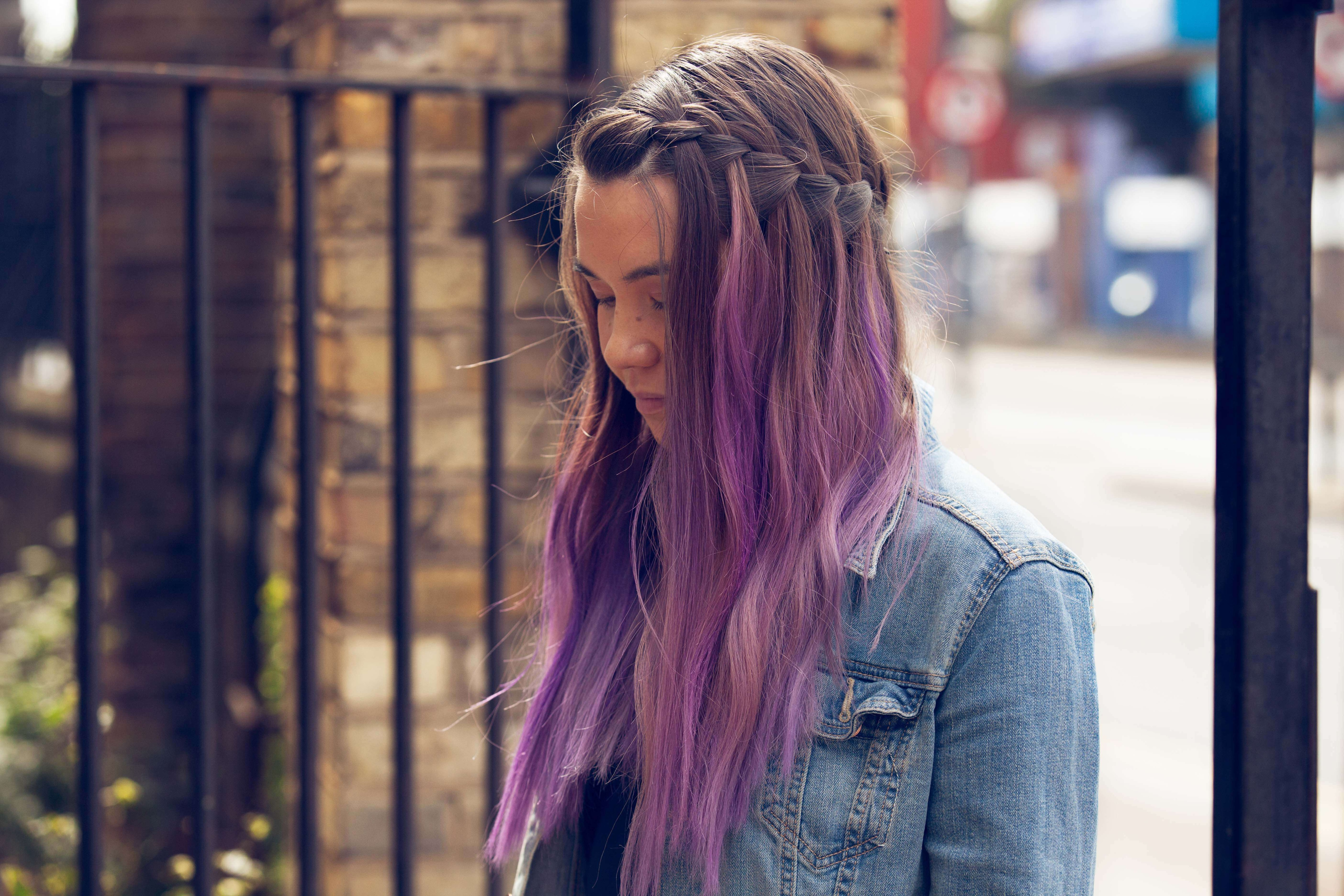 French braids: side view of a young woman with purple ombre hair and a French waterfall braid