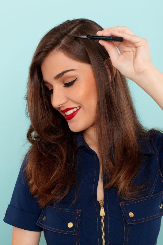 How to use a curling wand: Close-up of a brunette sectioning her hair with a comb