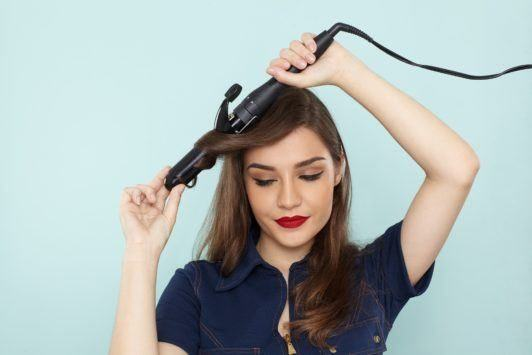 How to use a curling wand: Brunette using a curling wand to curl a front section of her hair