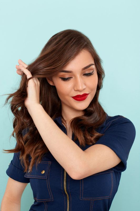 How to use a curling wand: Woman with brunette wavy hair combing through her hair with her fingers