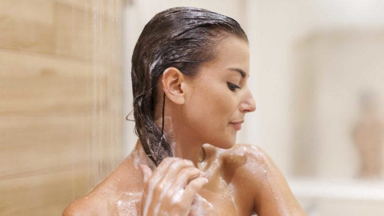 brunette woman in the shower washing her hair