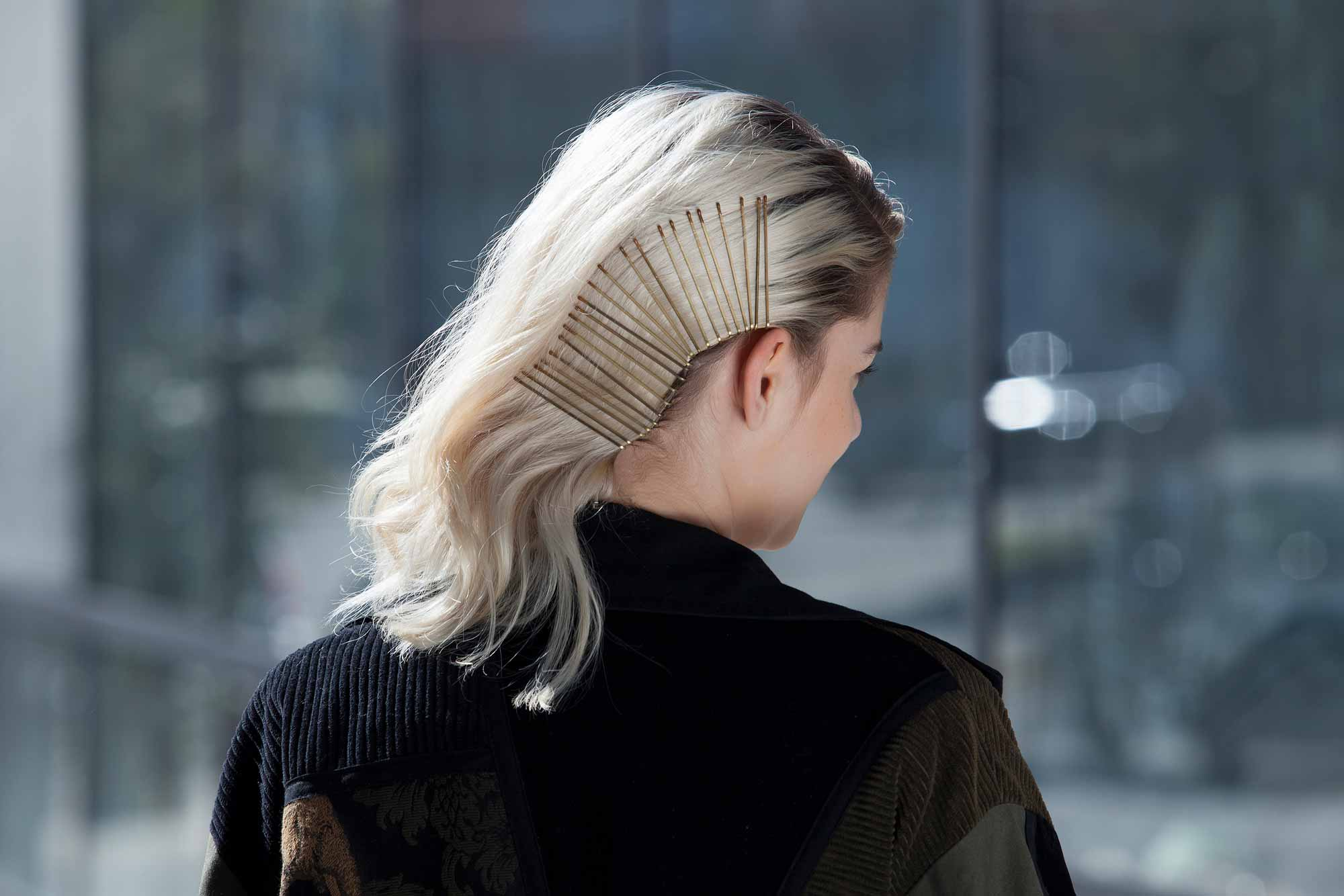 Bobby pin hairstyles: Closeup shot of a woman with side-swept bleach blonde hair styled with bobby pins