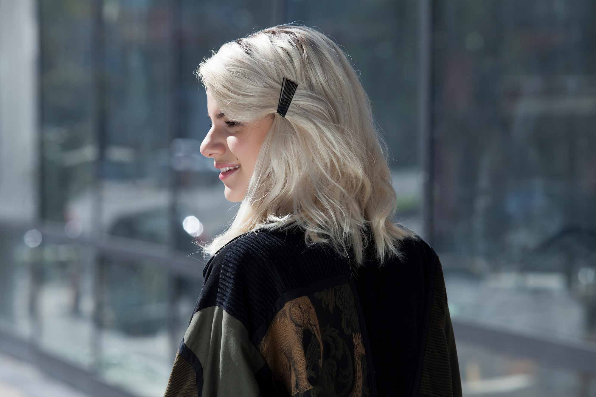 Bobby pin hairstyles: close up shot of a woman with platinum blonder hair with bobby pinned back fringe