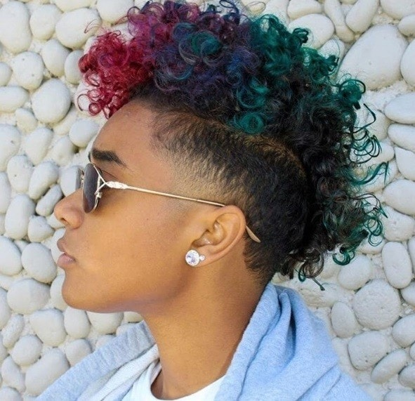 close up shot of woman with a watermelon dyed curly mohawk, wearing sunglasses, a blue top and posing outside