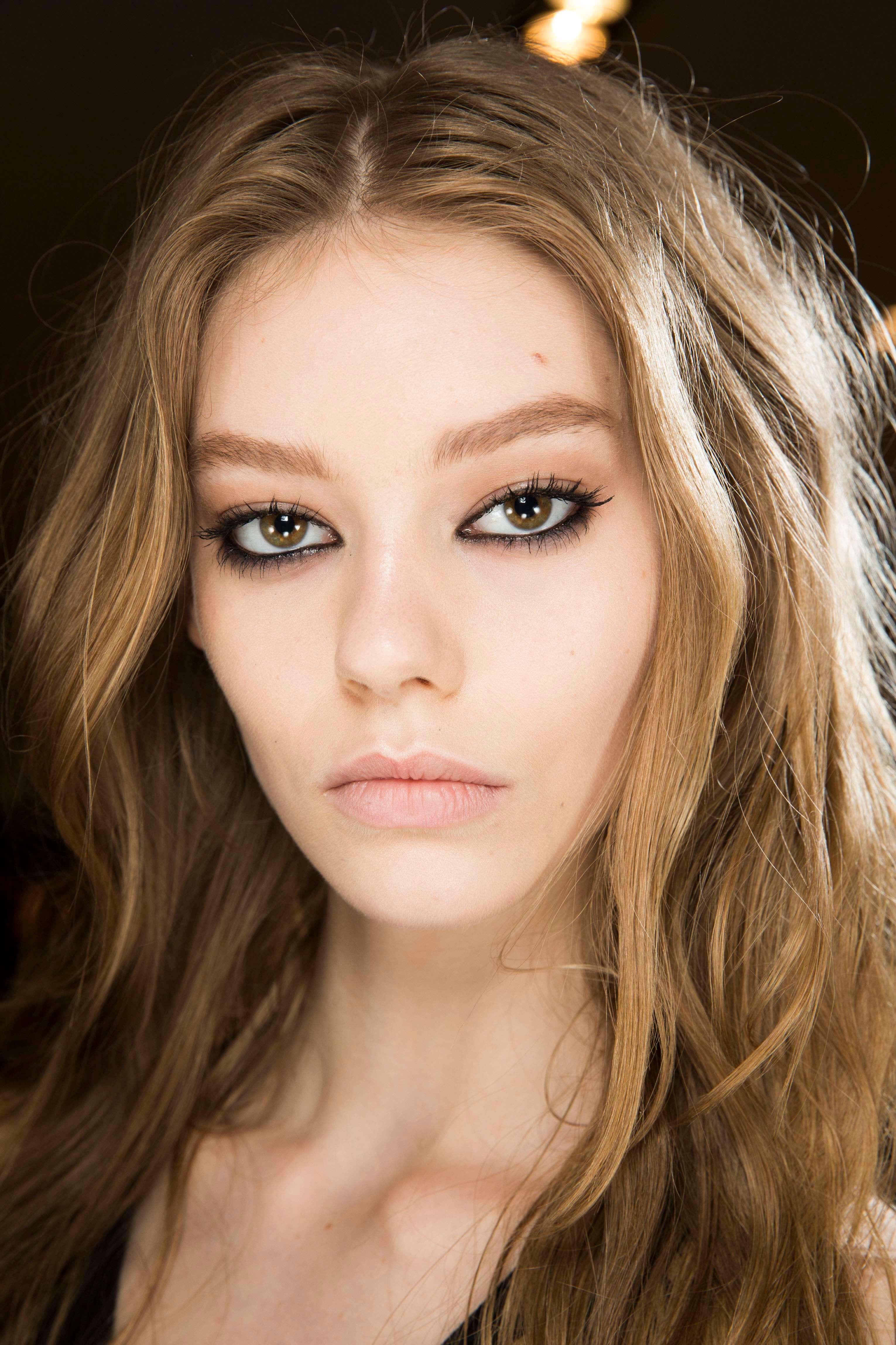 Shades of blonde hair: Woman with dark blonde bronde wavy hair wearing heavy eye makeup.