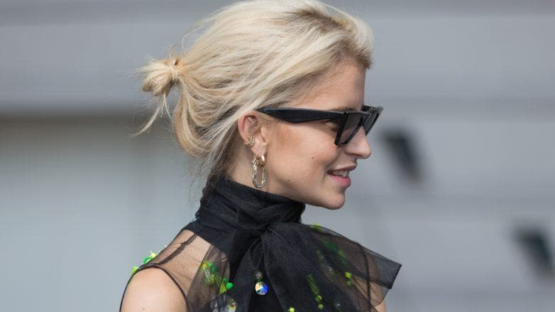 Best shampoo for fine hair: Caroline Daur with her short, bleach blonde fine hair styled into a messy bun updo, wearing sunglasses with black dress on the street