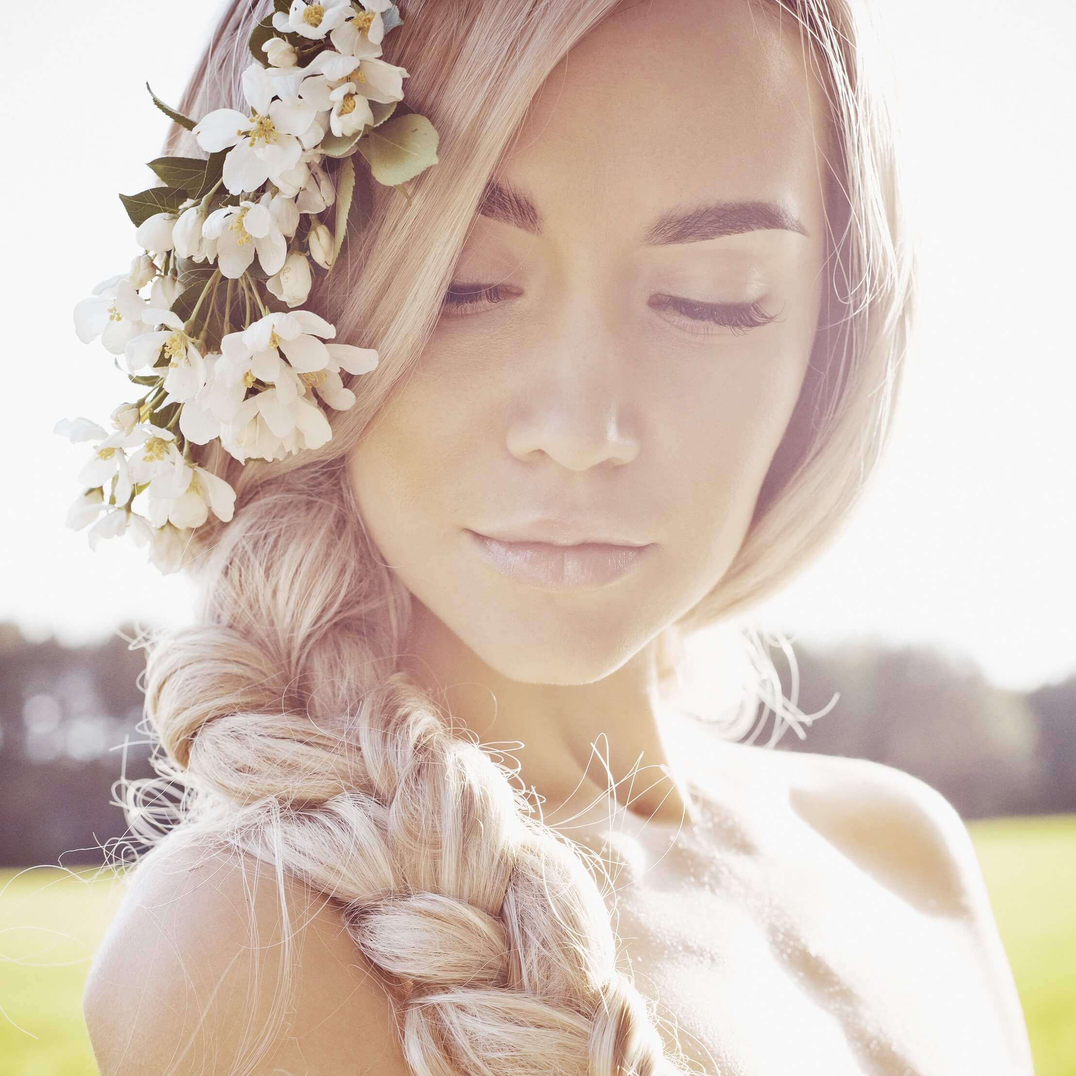 blonde model with long hair styled in a side braid with flowers placed at the top of the braid