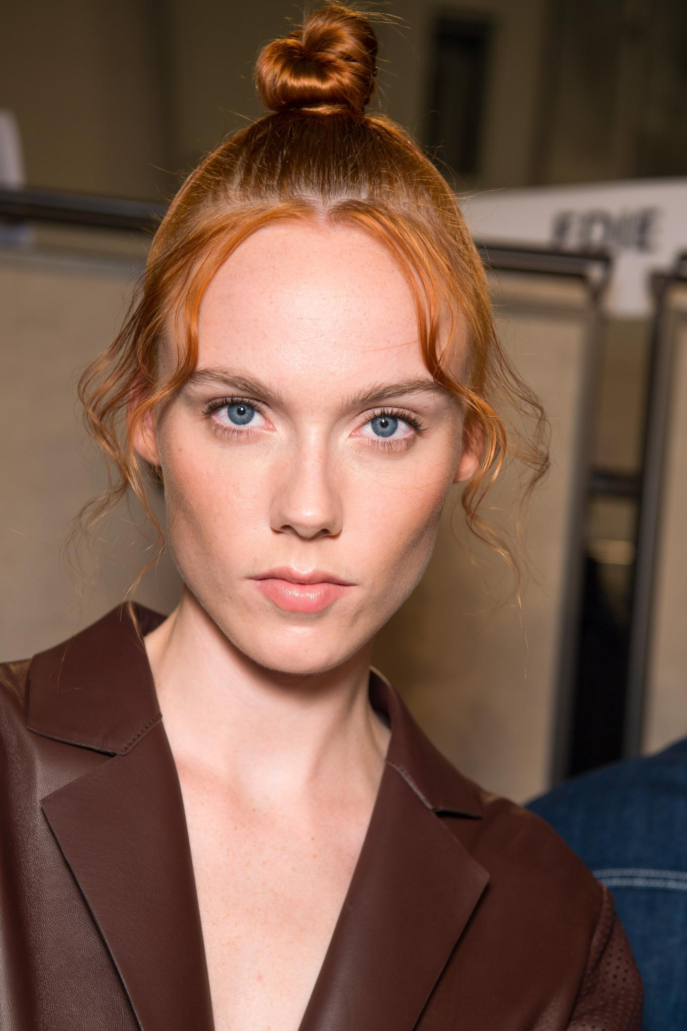 Co-washing hair guide: Shot of a model with ginger hair styled into a messy topknot