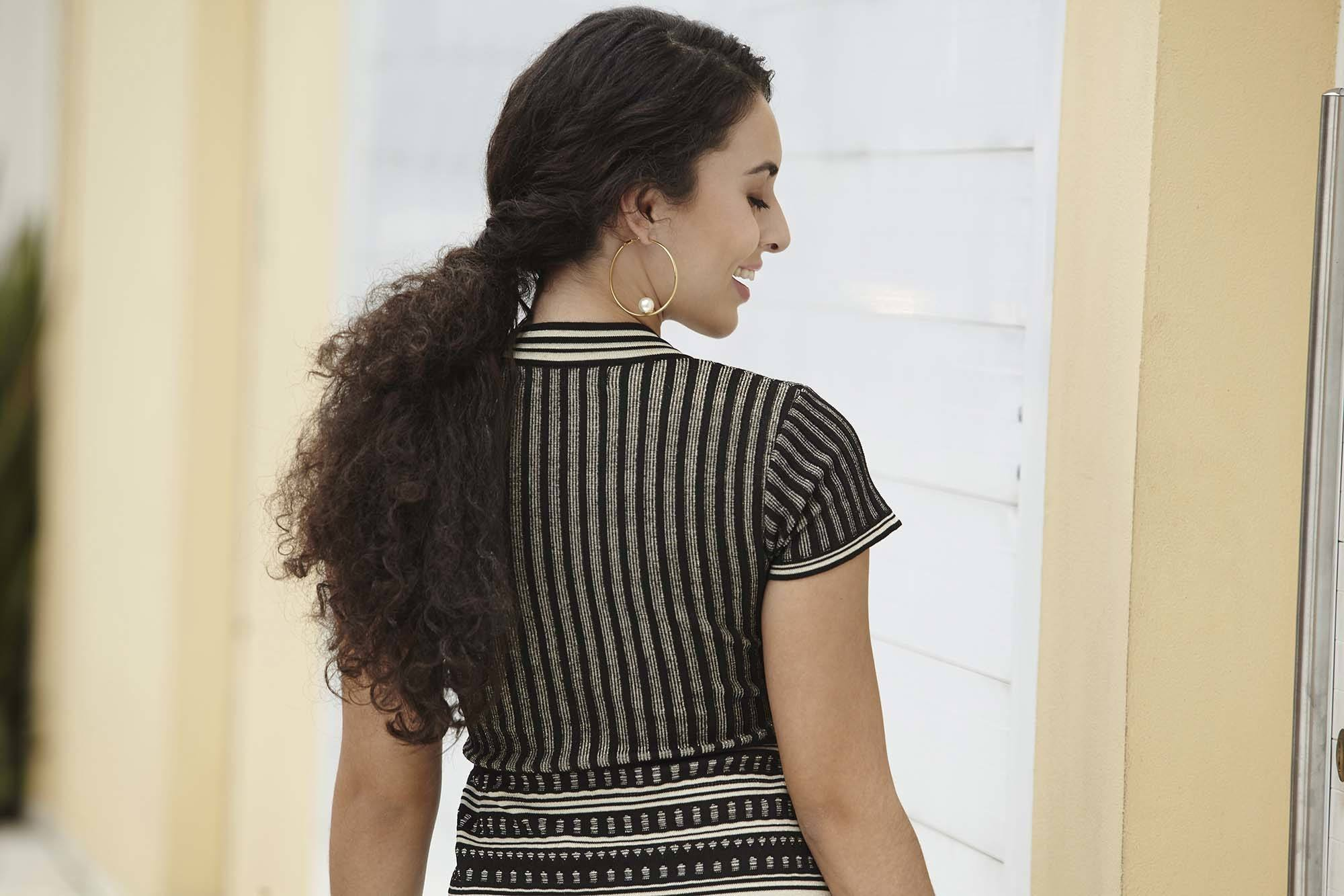 Long curly hair: Close up shot of a woman with long dark brown curly hair wearing striped dress and posing outside